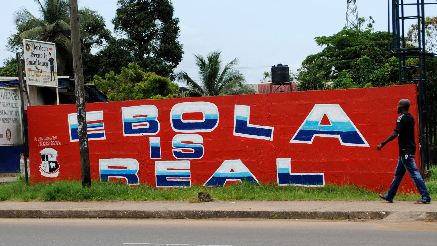 """A man walks by a mural reading """"Ebola is real"""" in Monrovia, Liberia, October 12, 2014. Ebola, a hemorrhagic fever, has killed more than 4,000 people since March in an epidemic centered around Liberia, Guinea and Sierra Leone. REUTERS/James Giahyue"""