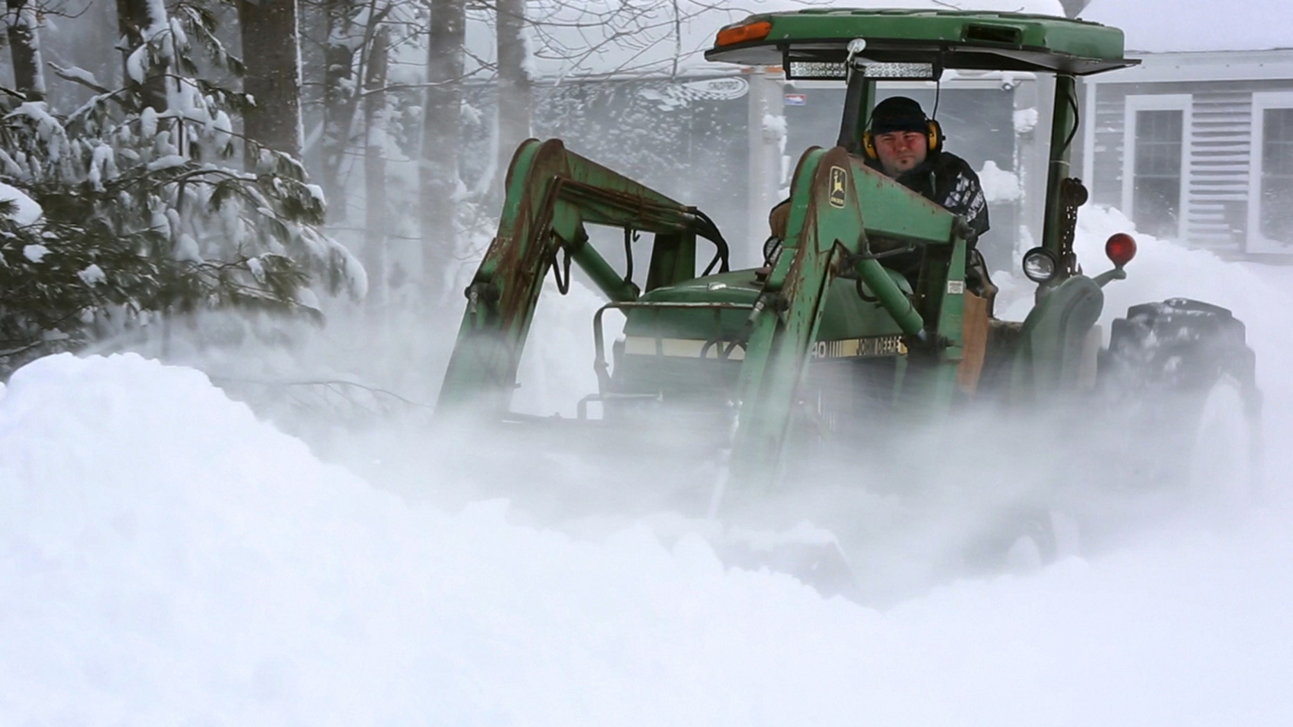 Alan Boucher uses a farm tractor to dig out of his driveway during a blizzard, Monday, Feb. 13, 2017, in Freeport, Maine.