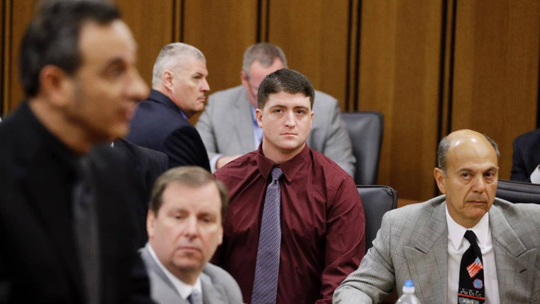 In this Dec. 17, 2014 photo, suspended Cleveland Police patrolman Michael Brelo, center, watches during a court hearing in Cleveland. A motion filed Tuesday, March 10, 2015, asks a Cuyahoga County judge in Cleveland to dismiss two voluntary manslaughter charges against 30-year-old Brelo. The attorneys argue that Brelo is immune from prosecution because he believed his life was in danger when he jumped on the hood of the suspects' car and fired as many as 15 rounds through the windshield following a high-speed chase in November 2012. (AP Photo/Tony Dejak)