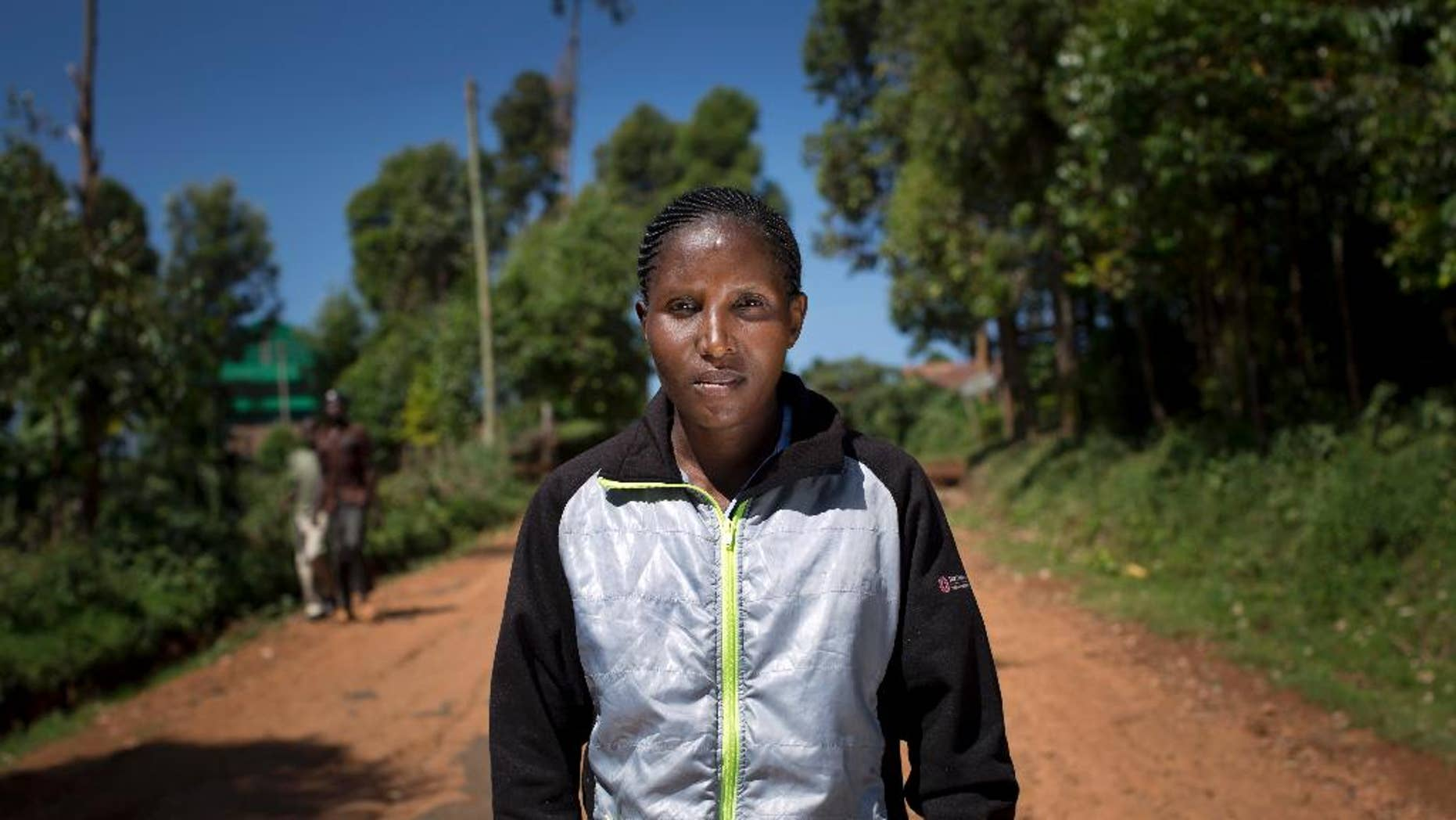 In this Monday, Feb. 1, 2016, photo, Kenyan runner Lilian Mariita poses for a portrait on the dirt road outside her house in the village of Nyaramba in western Kenya. The 27-year-old's racing career is over, and now she is back at square one: in Nyaramba, the muddy tea-plantation village in western Kenya she thought she'd escaped in 2011, when she left for the promise of a new life pounding American roads. (AP Photo/Ben Curtis)