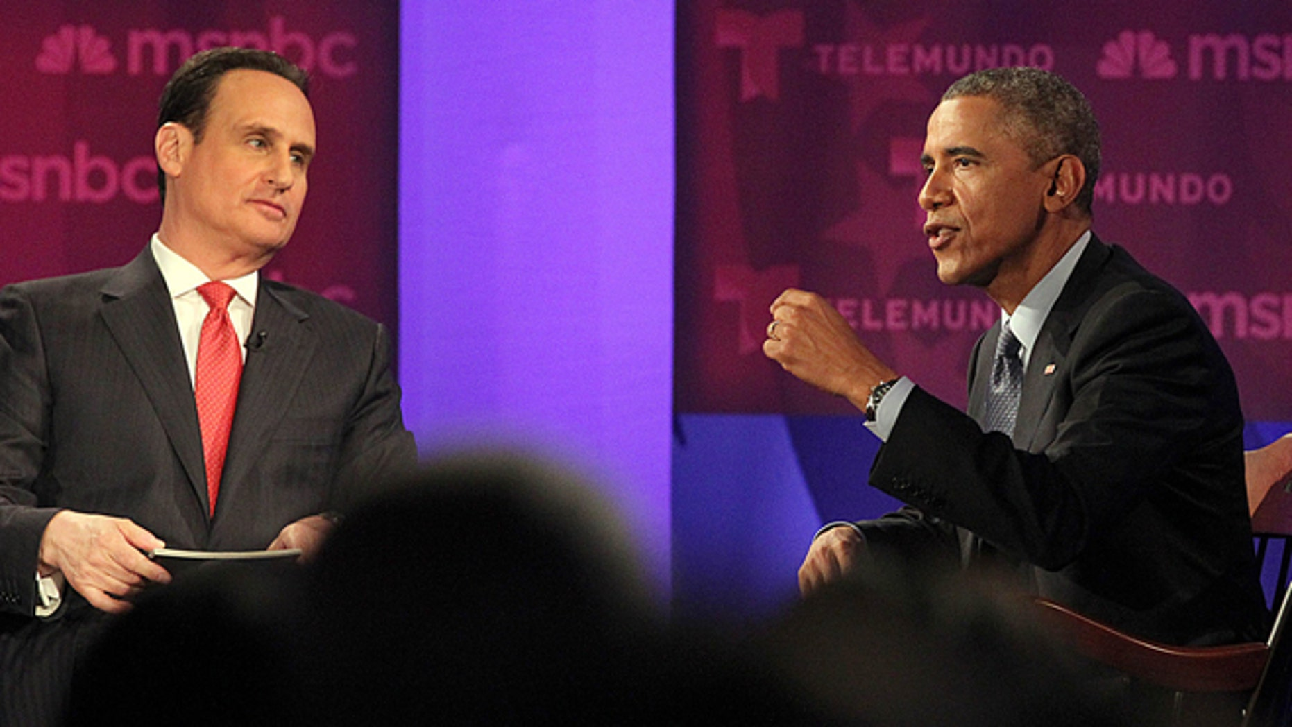 President Barack Obama, right, gestures during a town hall meeting on immigration with Jose Diaz-Balart, hosted by Telemundo and MSNBC, Wednesday, Feb. 25, 2015, at Florida International University in Miami. (AP Photo/El Nuevo Herald, Pedro Portal, Pool)