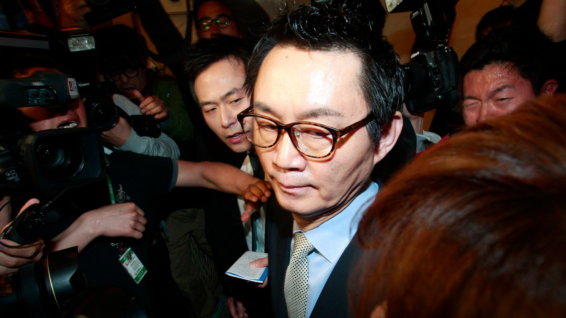 """South Korean President Park Geun-hye's spokesman Yoon Chang-jung surrounded by journalists leaves after a press conference in Seoul, South Korea, Saturday, May 11, 2013. Park fired Yoon because of what her office said Friday was a """"disgraceful incident"""" during Park's trip to the United States, in what could be a domestic blow after an otherwise widely praised appearance in Washington. Without elaborating, the presidential Blue House said on its website that unspecified actions by Yoon marred the government's dignity. (AP Photo/Ahn Young-joon)"""