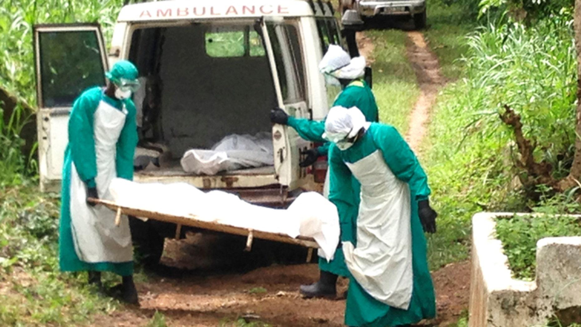 Health workers carry the body of an Ebola virus victim in Kenema, Sierra Leone, June 25, 2014. Picture taken June 25, 2014. REUTERS/Umaru Fofana