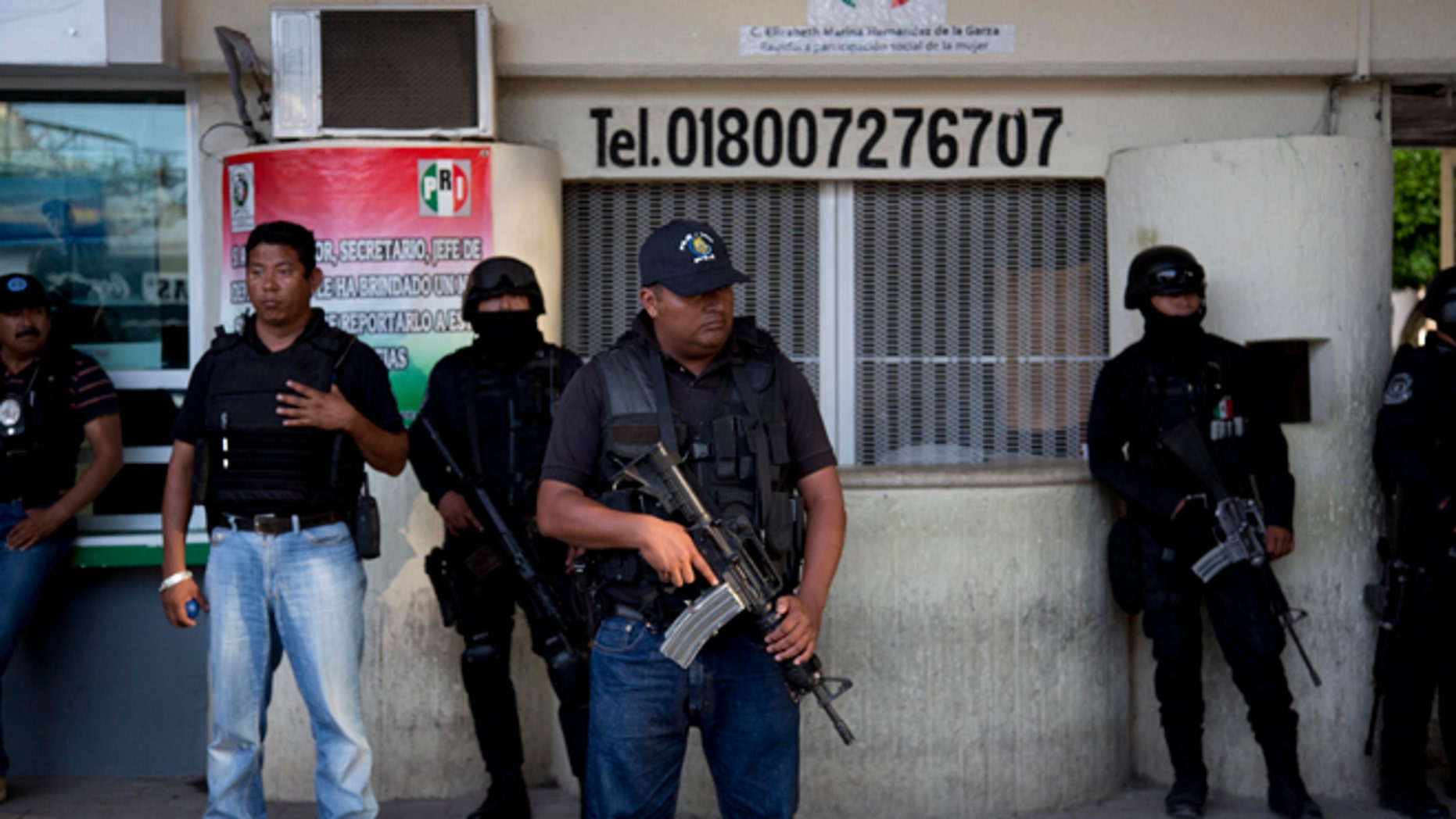 Police officers stand guard outside the municipality of Iguala, Mexico, Monday, Oct. 6, 2014. Federal officials on Monday disarmed local police and took over security after an attack on students that left at least six dead and 43 missing. Officials say that police officers were in league with a local gang called the Guerreros Unidos in carrying out the attack, and sent a new preventative unit of the federal police to keep order and help look for the missing. (AP Photo/Eduardo Verdugo)