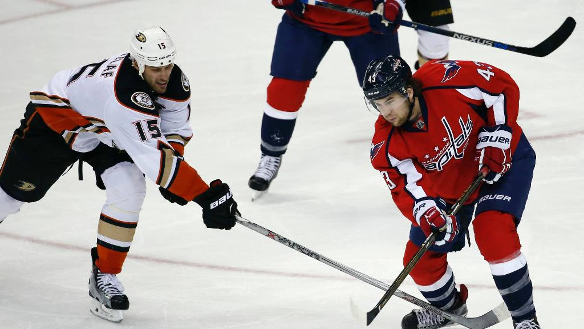 FILE - In this April 10, 2016 file photo, Washington Capitals right wing Tom Wilson (43) passes the puck as Anaheim Ducks center Ryan Getzlaf (15) defends during an NHL hockey game in Washington. Wilson's knee-on-knee hit on Pittsburgh's Conor Sheary cost him $2,404 in the form of a fine from the NHL, but the Washington Capitals forward escaped a suspension that could have altered the second-round playoff series against the Penguins.  (AP Photo/Alex Brandon, File)