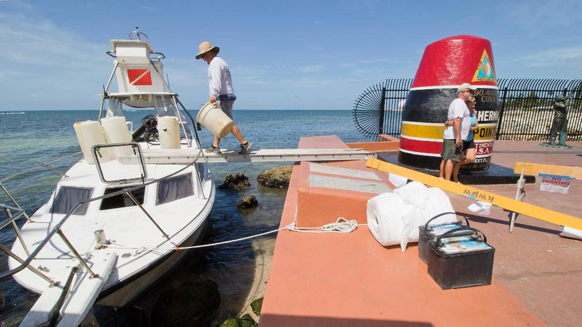 Environmental clean-up crews respond to a grounded dive boat that contained a group of Cuban migrants on Wednesday, July 13, 2016, at the Southermost Point marker in Key West, Fla. The group of three men and three women were taken into custody on Duval Street shortly thereafter and will be processed at the Krome Detention Center in Miami.  (Rob O'Neal(/The Miami Herald via AP)(/The Key West Citizen via AP)  MIAMI OUT; MANDATORY CREDIT