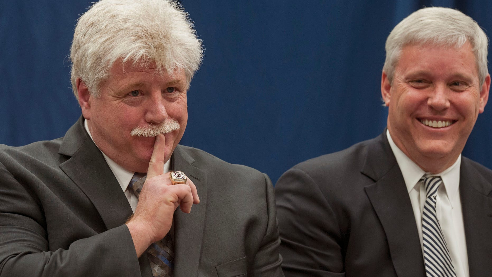 """Dennis """"Red"""" Gendron, left, gestures animatedly during a press conference where he was introduced as the new men's hockey coach by Athletic Director Steve Abbott, right, at the University of Maine, Tuesday, May 28, 2013, in Orono, Maine.  (AP Photo/Michael C. York)"""