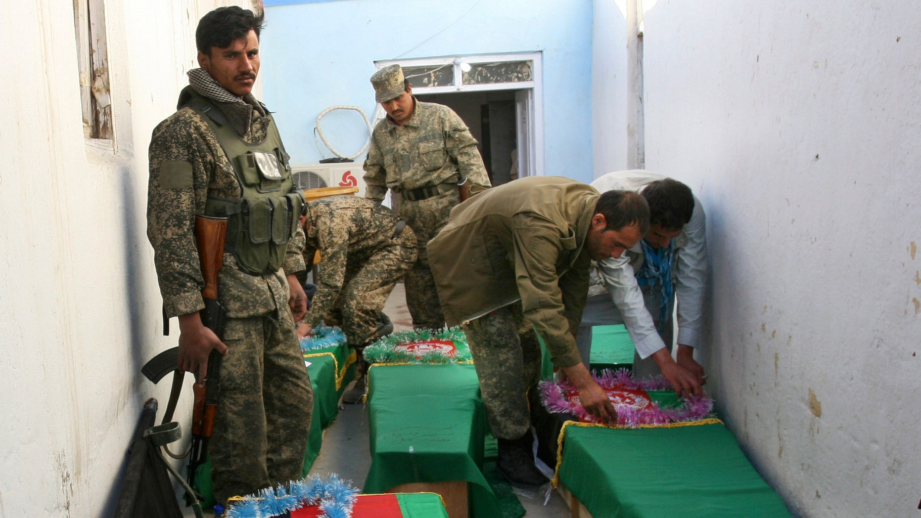 April 17, 2013: Afghan Army soldiers prepare the coffins for their killed comrades in the morgue of the main hospital in Ghazni, Afghanistan. A roadside bomb killed the five soldiers who were part of a government security force guarding a convoy of trucks in Ghazni's Qarabagh district. Roadside bombs and insurgent attacks killed dozens of people in five separate attacks across Afghanistan as violence steadily rises during this year's spring fighting season, officials said Wednesday.