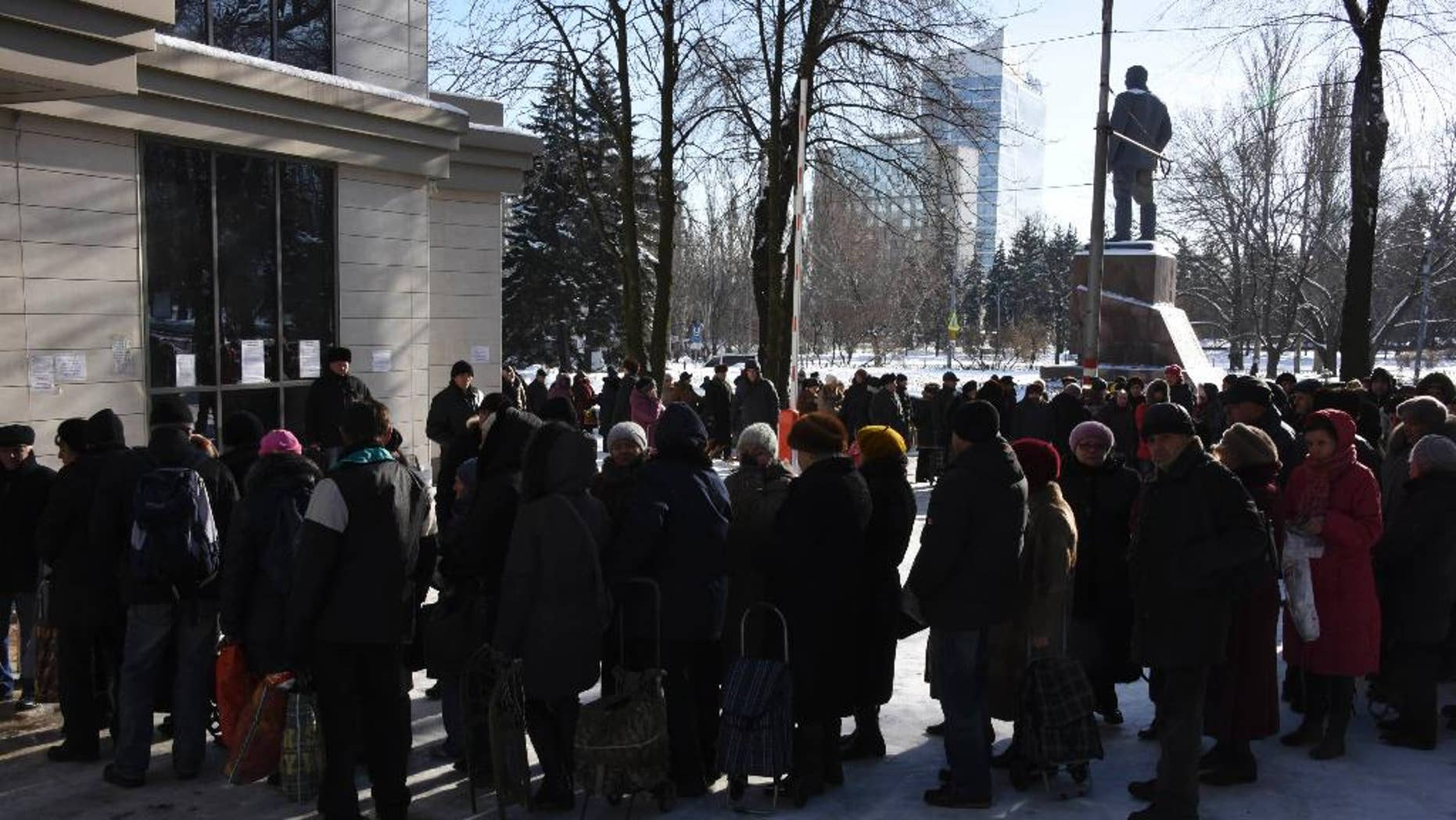People queue to receive humanitarian aid from the charitable foundation of Ukrainian billionaire Rinat Akhmetov, whose vast wealth is founded on the industrial output of Donetsk coal-rich region, in Donetsk, Eastern Ukraine, Tuesday, Jan. 13, 2015. Akhmetov is contentious figure in eastern Ukraine. Although a major provider of employment, he is regarded with profound suspicion by much of the impoverished local population. Still, his standing improves with every consignment of goods that reaches separatist-held regions. Amnesty International said it received reports before the New Year holidays of volunteer battalions fighting alongside Ukrainian government forces of preventing the Akhmetov convoys from getting through. The battalion justified their actions by arguing that the food and clothes in the trucks could ultimately help to support the separatist cause, Amnesty says. (AP Photo/ Mstyslav Chernov)