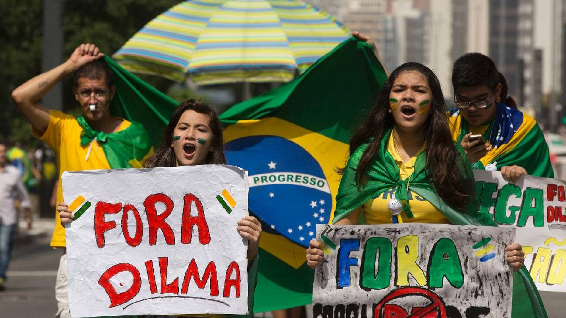 """Demonstrators shout anti-government slogans as they march holding signs that reads in Portuguese """"Dilma Out"""" and """"Corrupt Out"""", during a protest demanding the impeachment of Brazil's President Dilma Rousseff in Sao Paulo, Brazil, Sunday, April 12, 2015. It was the second such day of protests in less than a month and comes as polls show Rousseff with historically low approval ratings amid a corruption scandal at the state-run oil company, Petrobras, as well as a spluttering economy, a rapidly depreciating currency and political infighting. (AP Photo/Andre Penner)"""