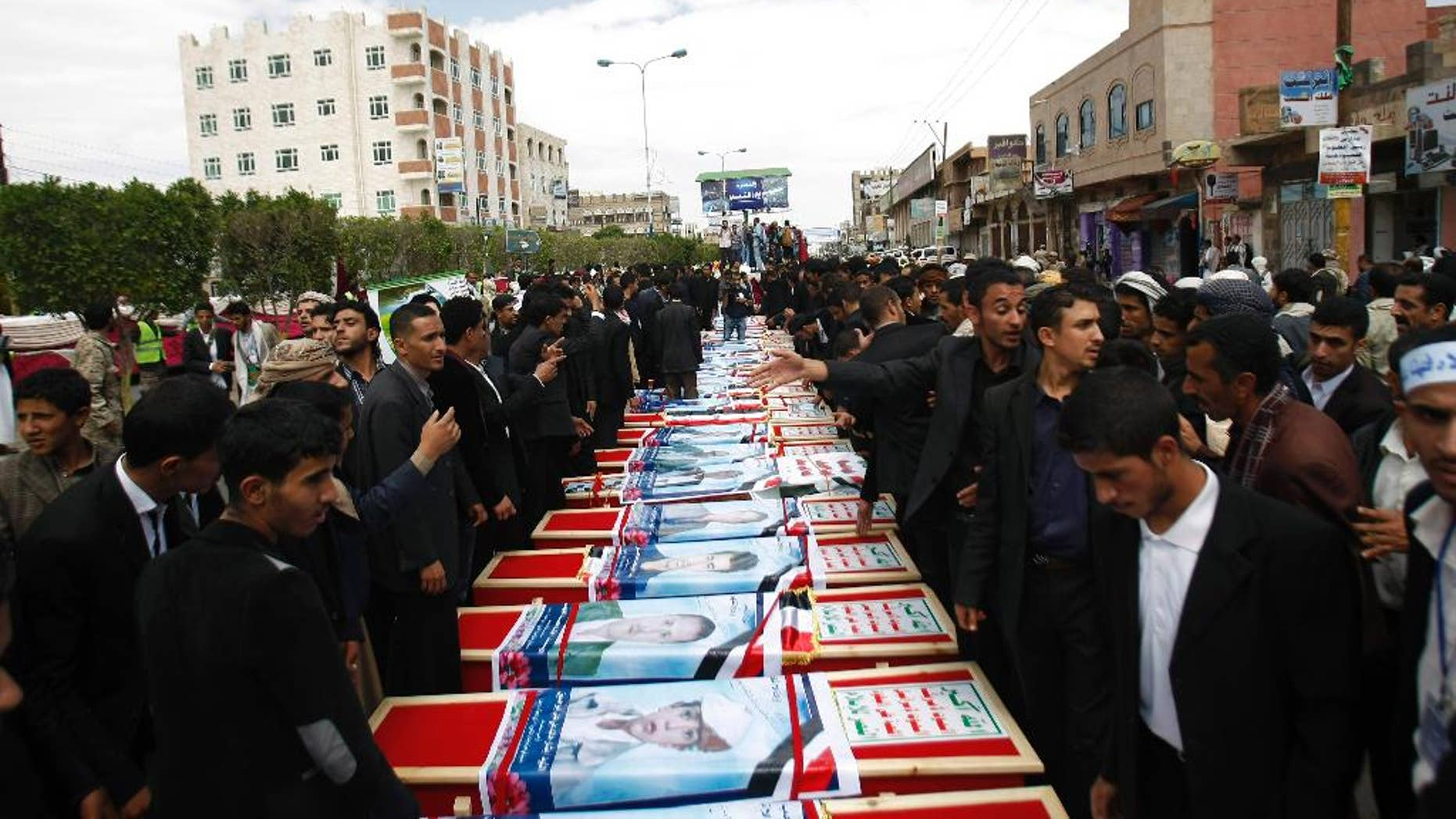Mourners stand near the coffins of a men who were killed last Thursday by a suicide bomber in central Sanaa, Yemen, Tuesday, Oct. 14, 2014.  Two suicide bombings in Yemen killed nearly 70 people last Thursday, with one targeting an anti-government rally by followers of the Houthi Shiite group,  who control Sanaa.  (AP Photo/Hani Mohammed)
