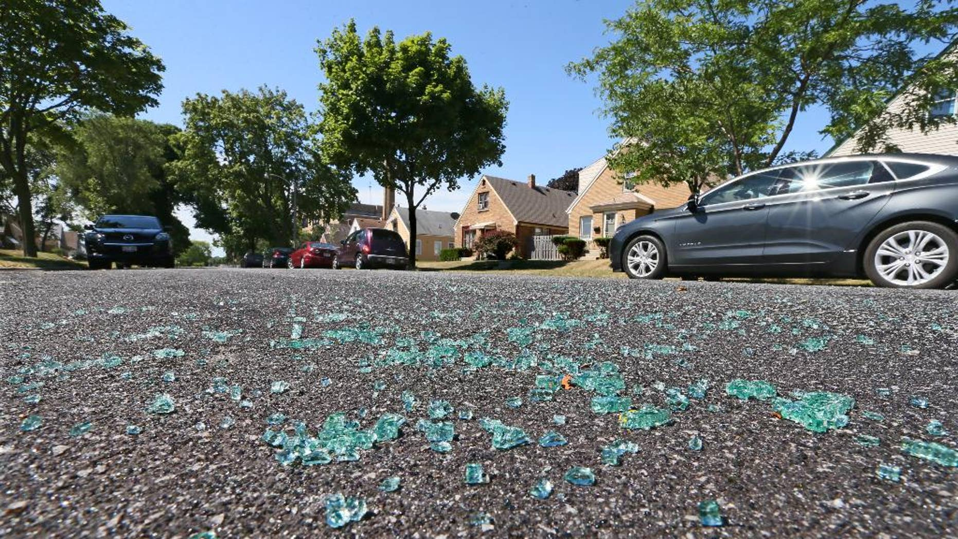 Broken auto glass is scattered in the street in the 3500 Blk. of S. 17th St. in Milwaukee, where a Milwaukee Police officer was shot while seated in the front seat of his squad car early Sunday, July 17, 2016.  A domestic violence suspect opened fire on the officer, who was sitting in his squad car early Sunday, seriously wounding him before fleeing and apparently killing himself shortly afterward, authorities said.  (Michael Sears/Milwaukee Journal Sentinel via AP)