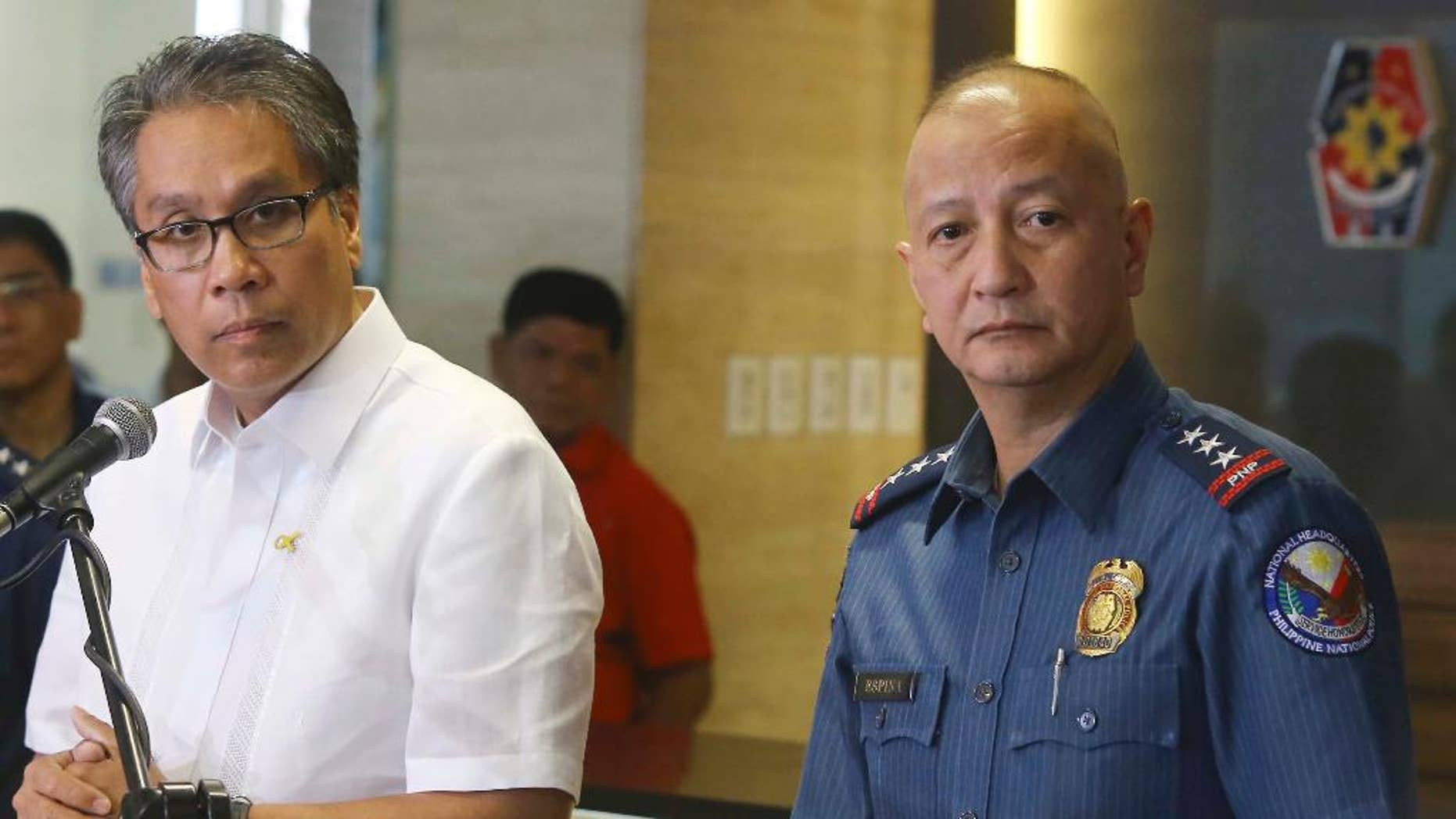 Philippine Interior and Local Government Secretary Mar Roxas, left, and Philippine National Police Deputy Director General Leonardo Espinal, right, listen to a reporter's questions during a news conference on Sunday's killing of at least 44 anti-terror commandos in the southern Philippines, Tuesday, Jan. 27, 2015 in Manila, Philippines. The government's biggest single-day combat loss in recent memory shocked many and led to fears it could endanger a recent peace deal signed with the biggest Muslim rebel group. (AP Photo)