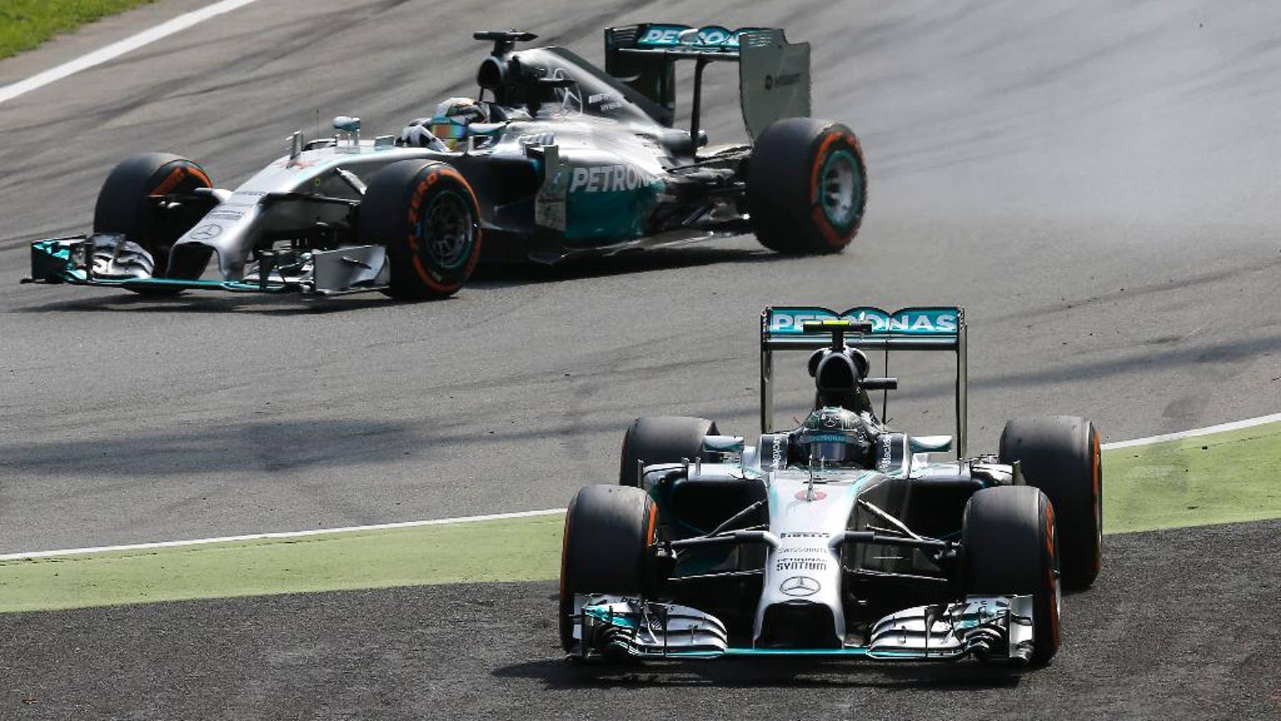 Mercedes driver Nico Rosberg of Germany, foreground, drives off the track while his teammate Mercedes driver Lewis Hamilton of Britain overtakes him during the Italian Formula One Grand Prix at the Monza racetrack, in Monza, Italy, Sunday, Sept. 7, 2014. (AP Photo/Antonio Calanni)