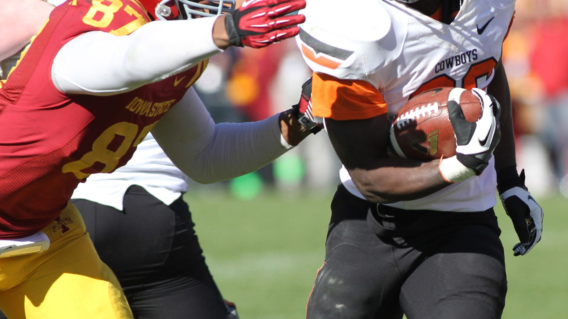 Oklahoma State running back Desmond Roland (26) breaks away from Iowa State defensive lineman David Irving (86) during the second half of an NCAA college football game in Ames, Iowa Saturday, Oct. 26, 2013. Oklahoma State won the game 58-27.(AP Photo by Justin Hayworth)