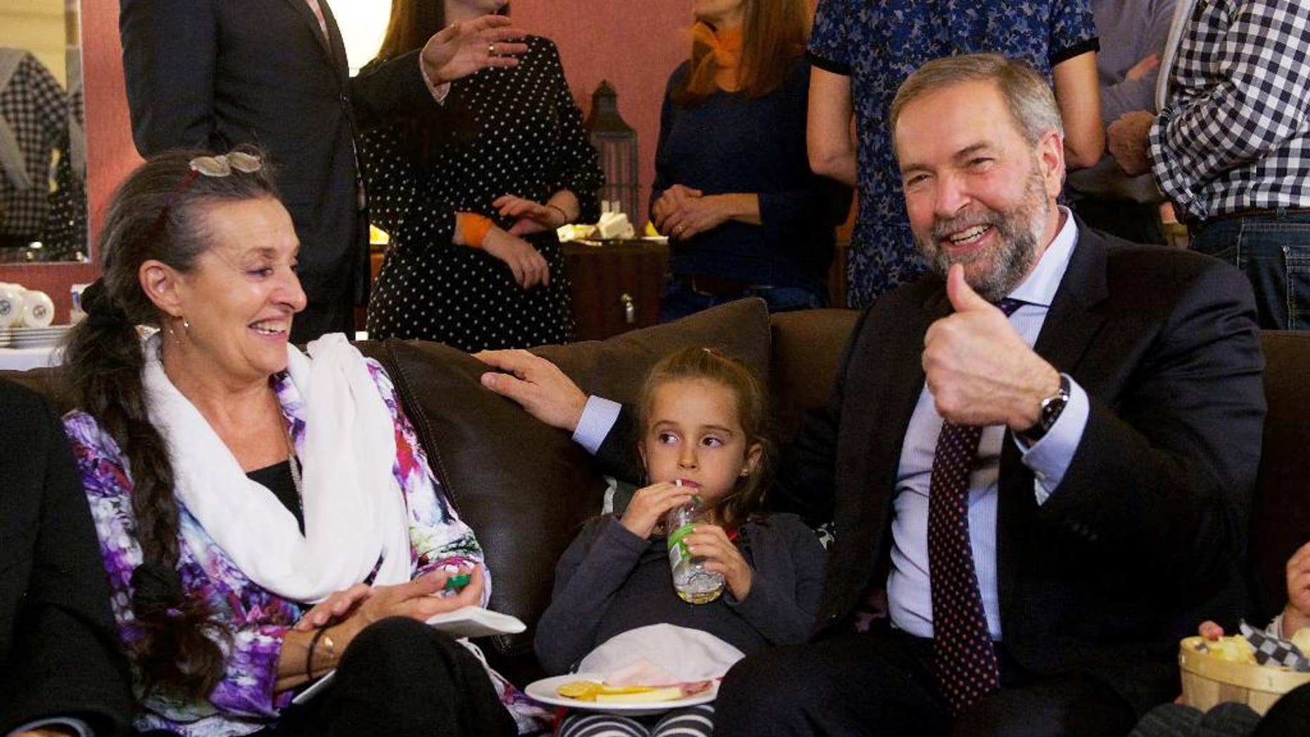 New Democratic Party Leader Tom Mulcair gestures as he watches the election results come in with his wife Catherine and granddaughter Juliette, Monday, Oct. 19, 2015, in Montreal. (Ryan Remiorz/The Canadian Press via AP) MANDATORY CREDIT