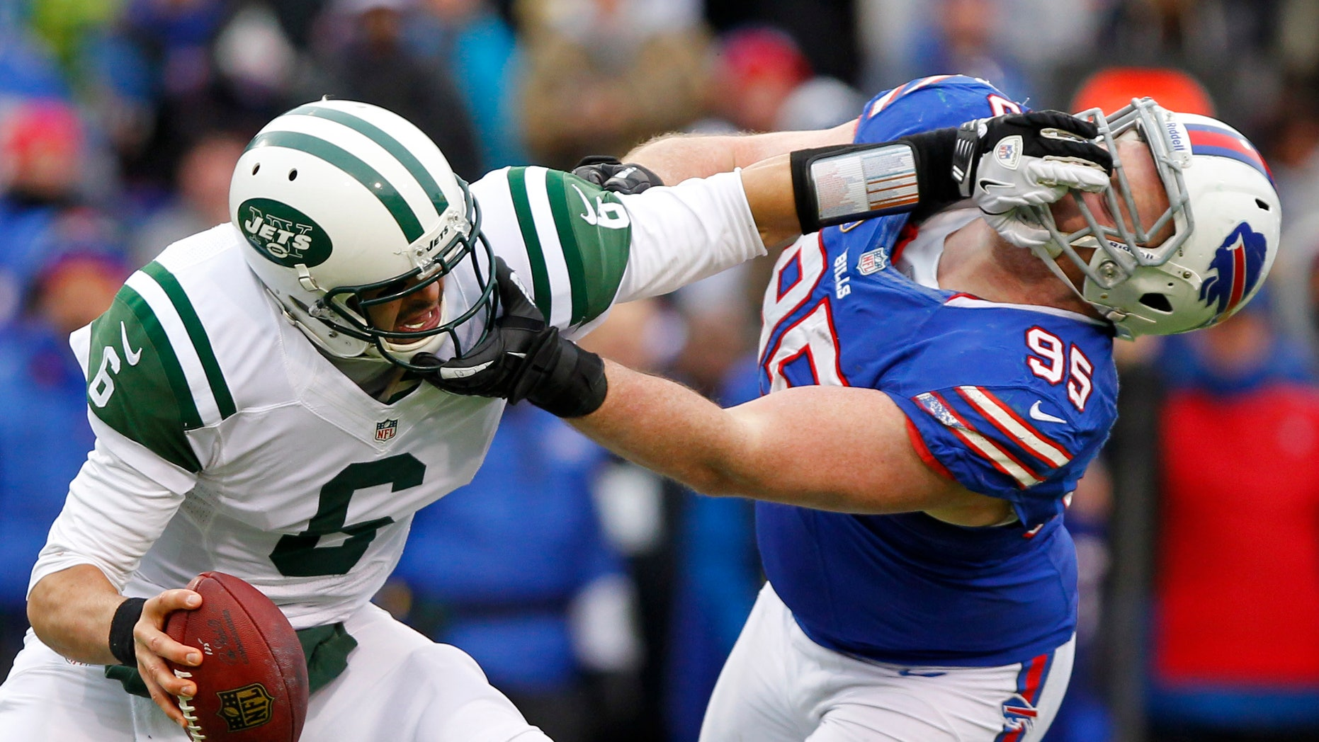 New York Jets quarterback Mark Sanchez (6) holds off Buffalo Bills defensive tackle Kyle Williams (95) during the second half of an NFL football game on Sunday, Dec. 30, 2012, in Orchard Park, N.Y. Buffalo won 28-9. (AP Photo/Bill Wippert)