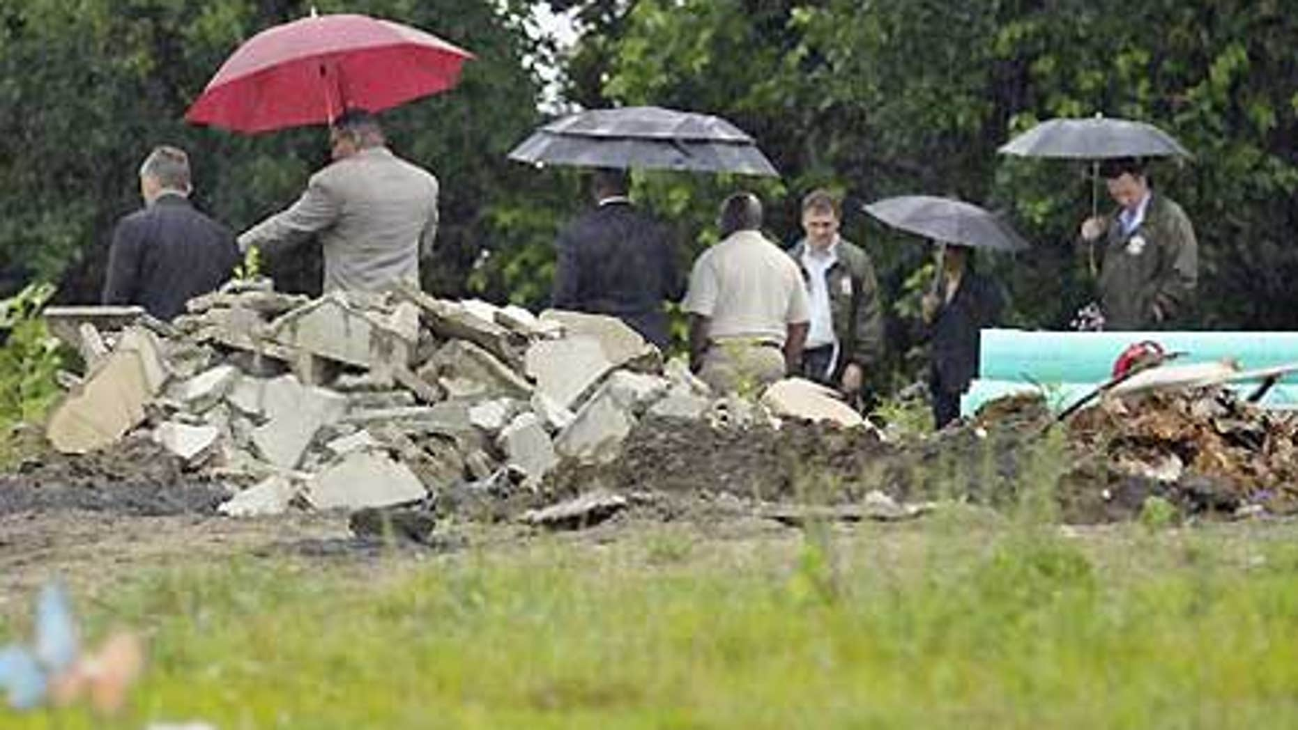 July 8: Authorities at Burr Oak Cemetery in Alsip, Ill., where dozens of graves were dug up and bodies dumped in a massive pile.