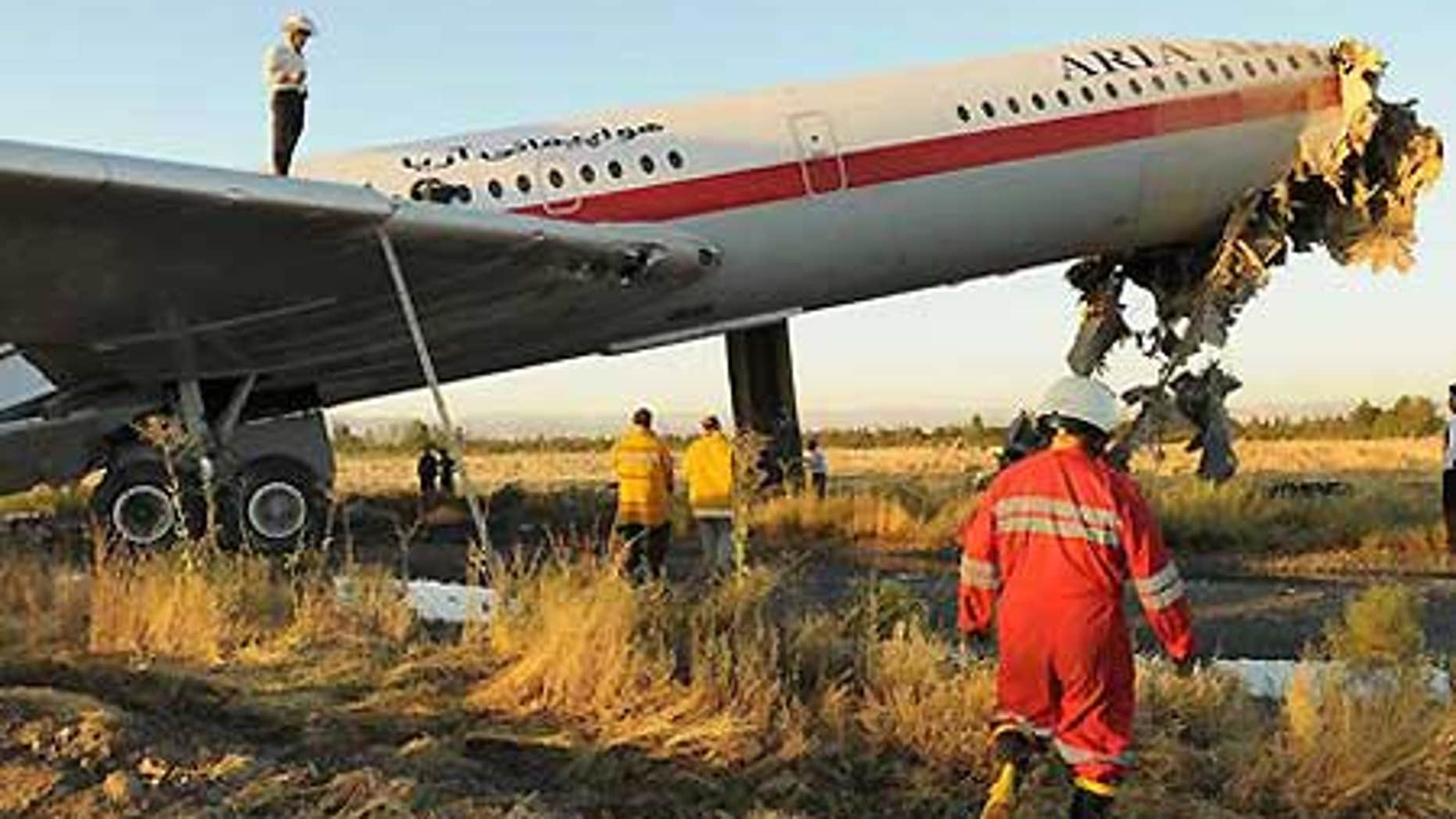 July 24: Emergency workers at the scene of an Iranian passenger plane crash just off the runway at the airport in Mashhad, northeast of Tehran, Iran.