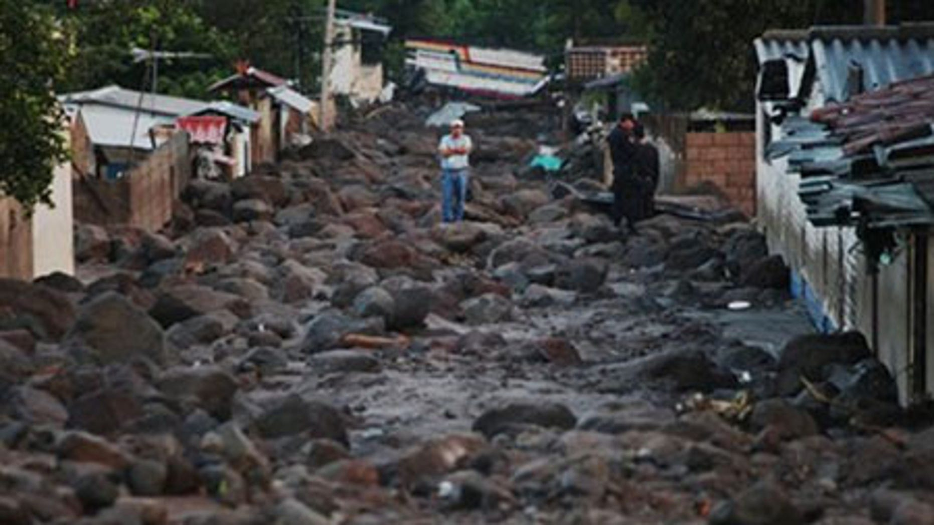 A man stands in a street covered with rocks from a landslide in Verapaz, some 125 km east from San Salvador, Monday, Nov. 9, 2009.