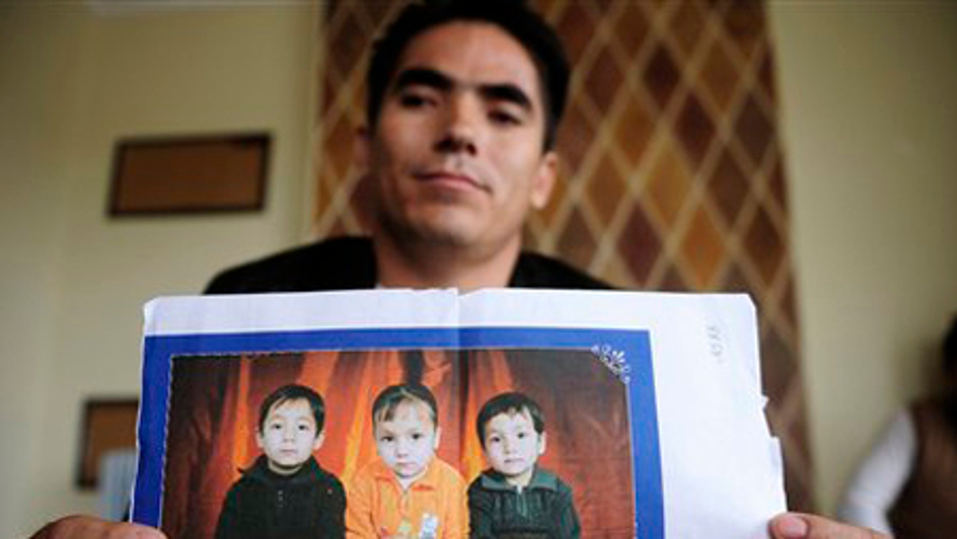Ali Khosh Razaee holds pictures of his three young children at a house in an Adelaide, Australia, suburb.