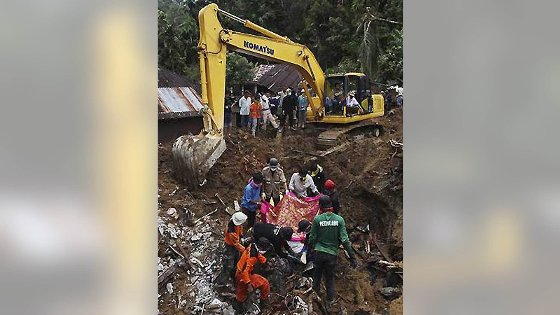 Oct. 4: Indonesian rescue volunteers cover a body before removing it from an area hit by landslides in the Sumatran Island village of Jumanak.
