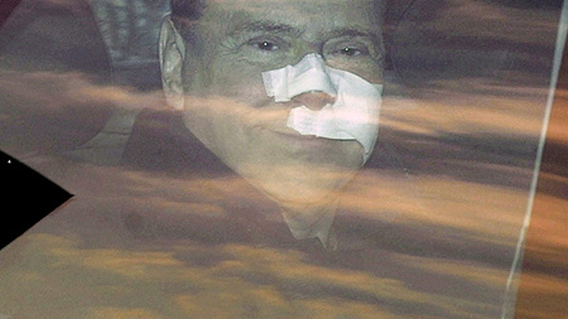 Dec. 17: Italian Premier Silvio Berlusconi, his face bandaged, leaves a Milan hospital.