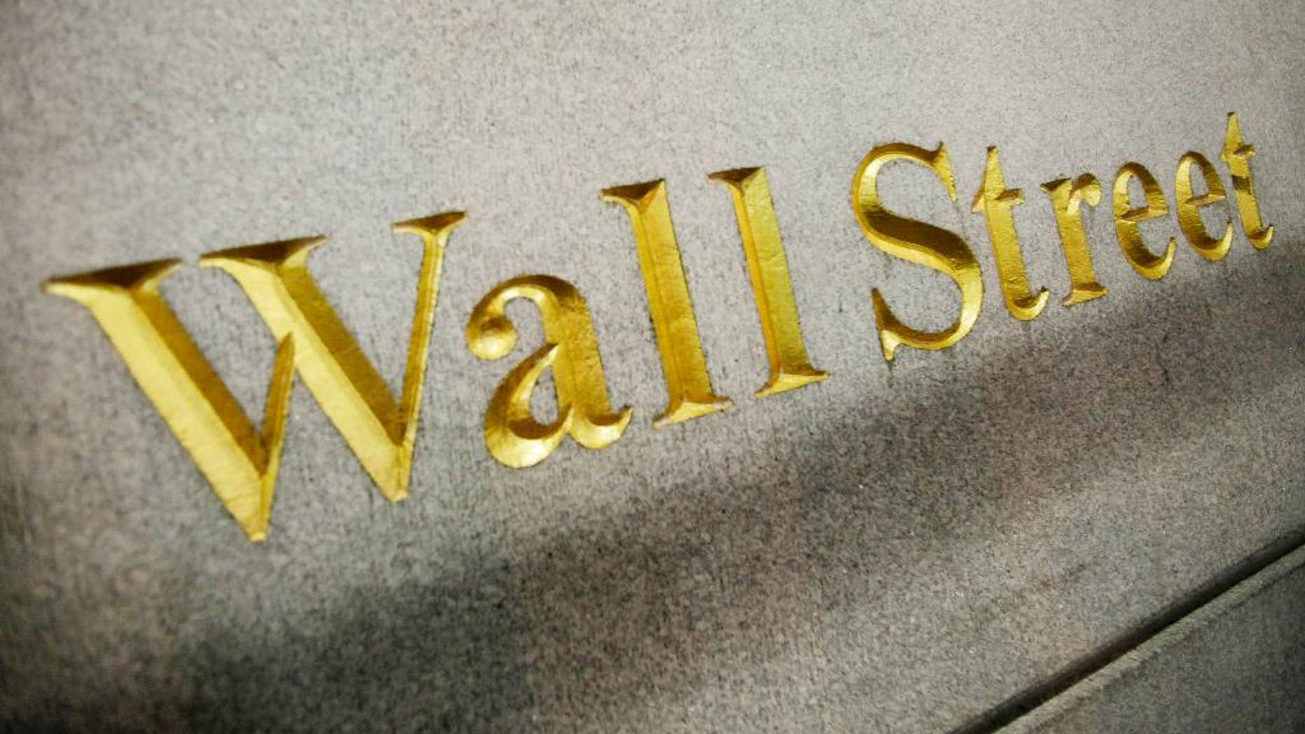 FILE - This Oct. 8. 2014 photo shows a Wall Street address carved into the side of a building in New York. U.S. stock indexes are opening lower Monday, April 6, 2015 following a weak jobs report late last week. (AP Photo/Mark Lennihan, File)