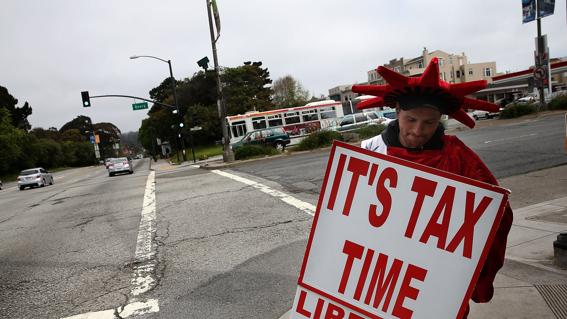 SAN FRANCISCO, CA - APRIL 14:  Aaron Lee holds a sign advertising income tax services for Liberty Tax Service on April 14, 2014 in San Francisco, California.  Tax preparers are helping last minute tax filers ahead of the April 15th deadline to file state and federal income taxes. The Internal Revenue Service is expecting an estimated 35 million returns in the week leading up to the deadline.  (Photo by Justin Sullivan/Getty Images)
