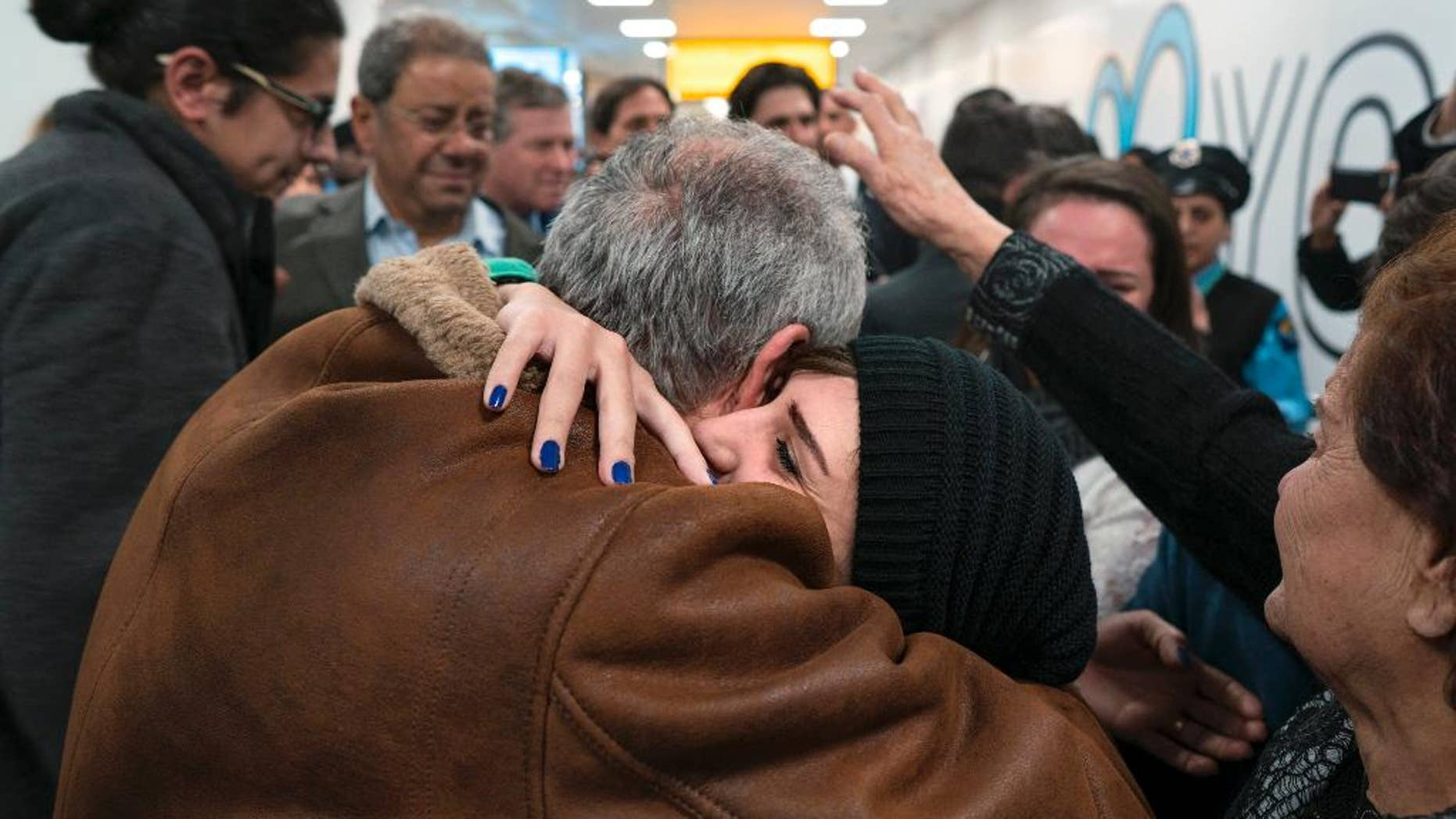 """FILE - In a Monday, Feb. 6, 2017 file photo, family members who have just arrived from Syria embrace and are greeted by family who live in the United States upon their arrival at John F. Kennedy International Airport in New York. Organizers in cities across the U.S. are telling immigrants to miss class, miss work and not shop on Thursday, Feb. 16, 2017,  as a way to show the country how important they are to America's economy and way of life. """"A Day Without Immigrants"""" actions are planned in cities including Philadelphia, Washington, Boston and Austin, Texas. (AP Photo/Craig Ruttle)"""