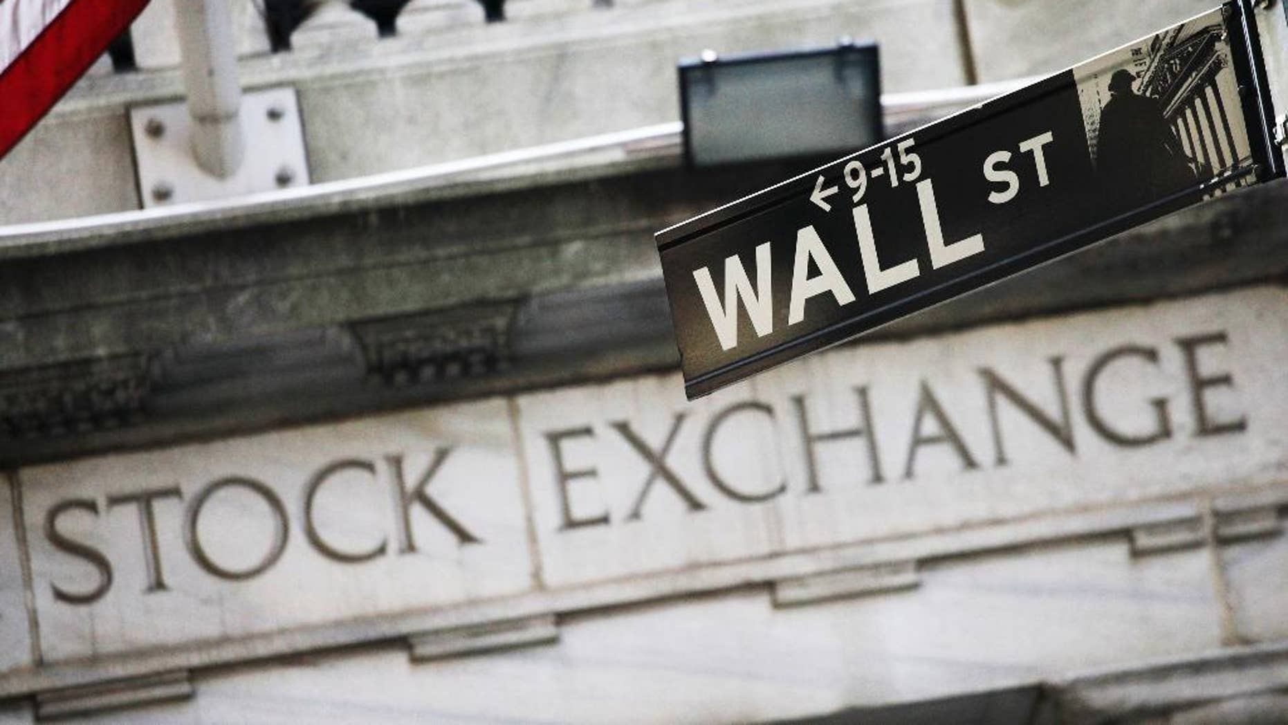 FILE - This July 16, 2013 file photo shows a Wall Street street sign outside the New York Stock Exchange in New York. U.S. stocks are starting the week sharply higher Monday, March 30, 2015, led by energy companies. (AP Photo/Mark Lennihan, File)