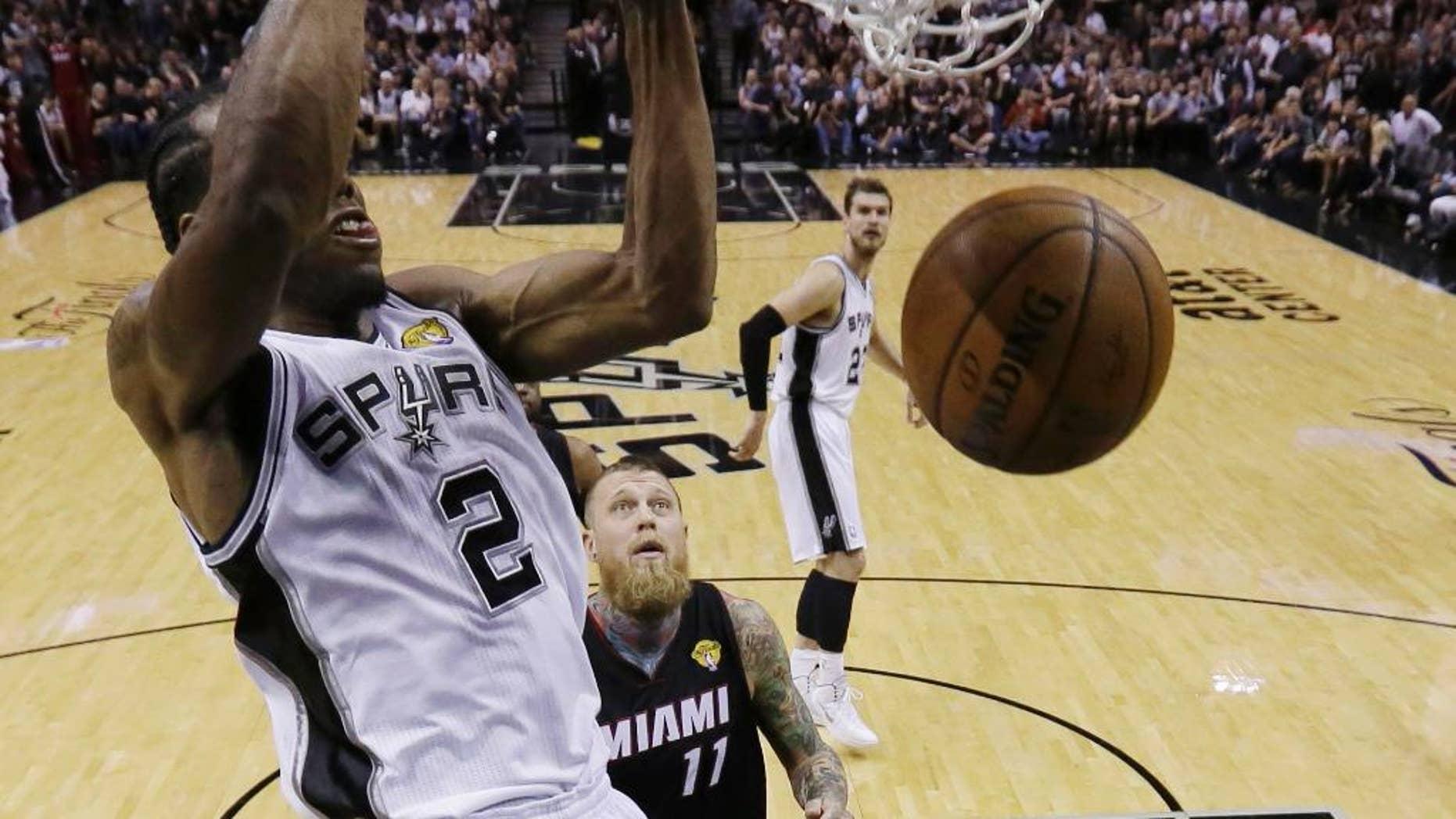 San Antonio Spurs forward Kawhi Leonard (2) dunks against the Miami Heat during the first half in Game 5 of the NBA basketball finals on Sunday, June 15, 2014, in San Antonio. (AP Photo/David J. Phillip, pool)