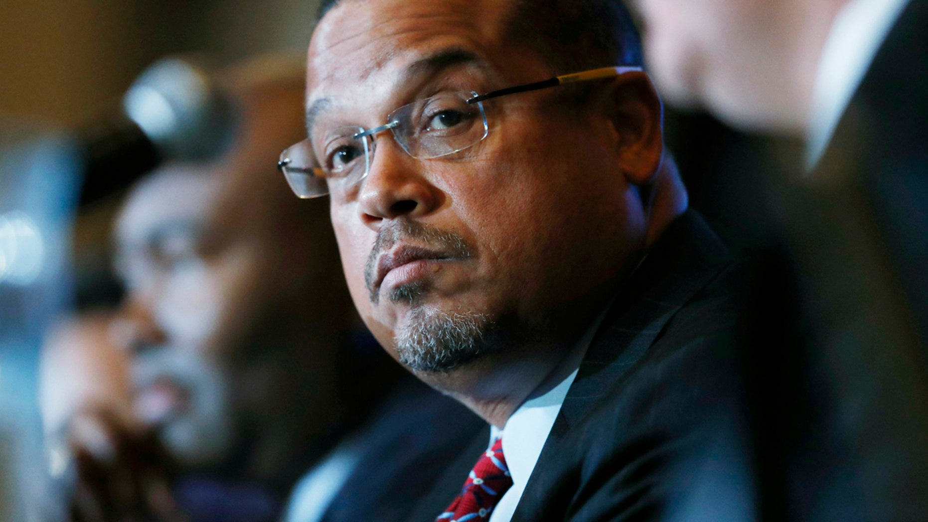 FILE - In a Dec. 2, 2016 file photo, U.S. Rep. Keith Ellison, D-Minn., listens with Jamie Harrison, back, chair of the South Carolina Democratic Party, as Ray Buckley, chair of the party in New Hampshire, speaks during a forum on the future of the Democratic Party, in Denver.