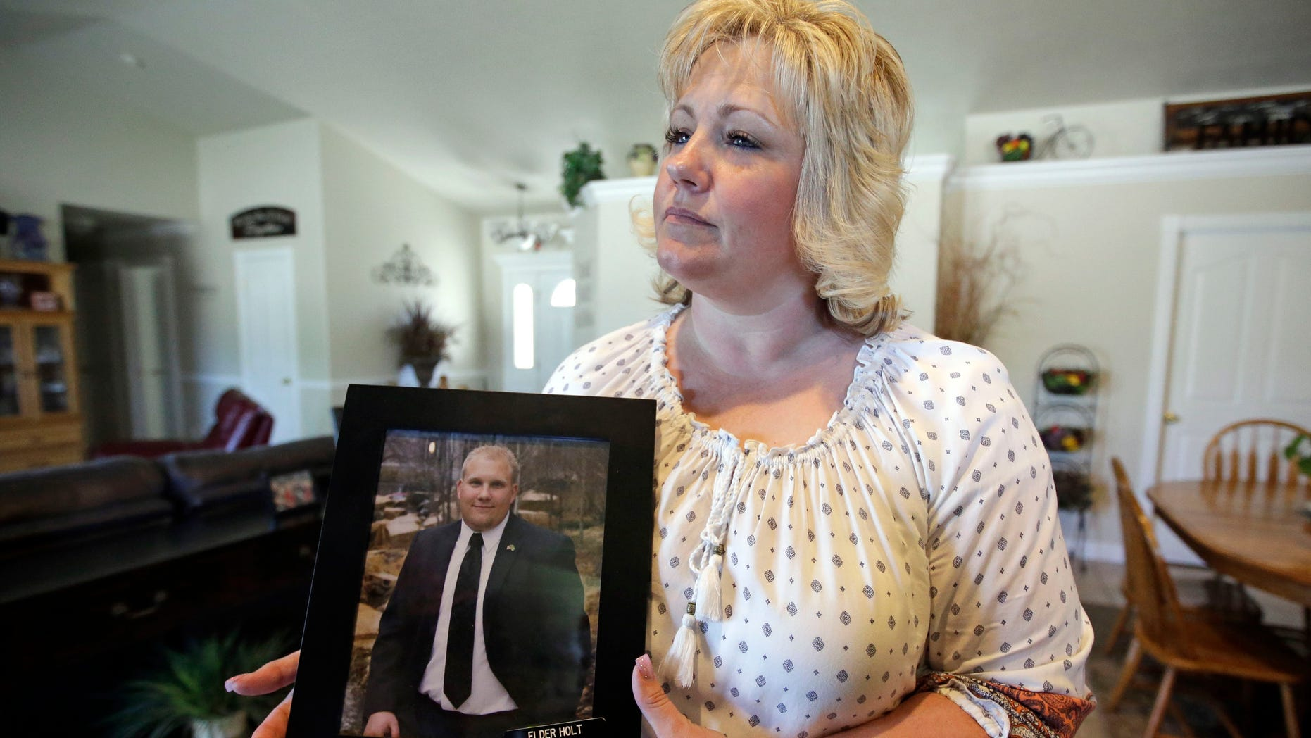 Laurie Holt holds a photograph of her son Josh Holt at her home, in Riverton, Utah, on July 13, 2016.