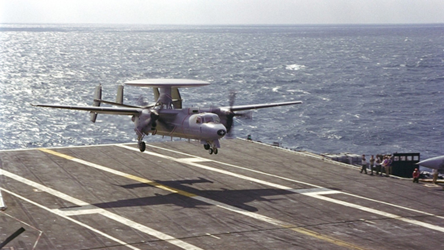 A Northrop Grumman E-2C Hawkeye 2000 surveillance and reconnaisance plane lands on a carrier.