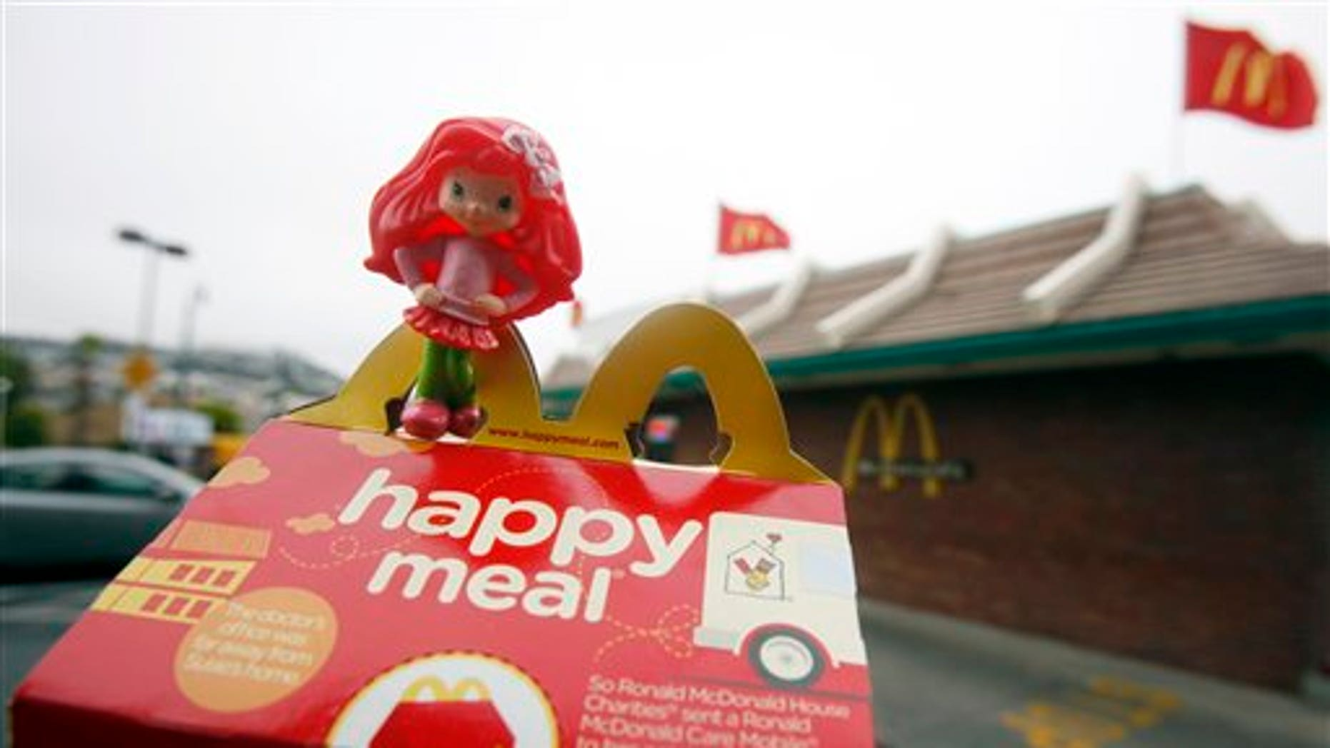 FILE - In this Oct. 1, 2010 file photo, a Happy Meal box and toy are shown outside of a McDonald's restaurant in San Francisco. City lawmakers on Tuesday, Nov. 2, 2010, approved legislation that they hope will force fast-food chains such as McDonald's to make their children's meals healthier or stop selling them with toys. (AP Photo/Jeff Chiu, File)