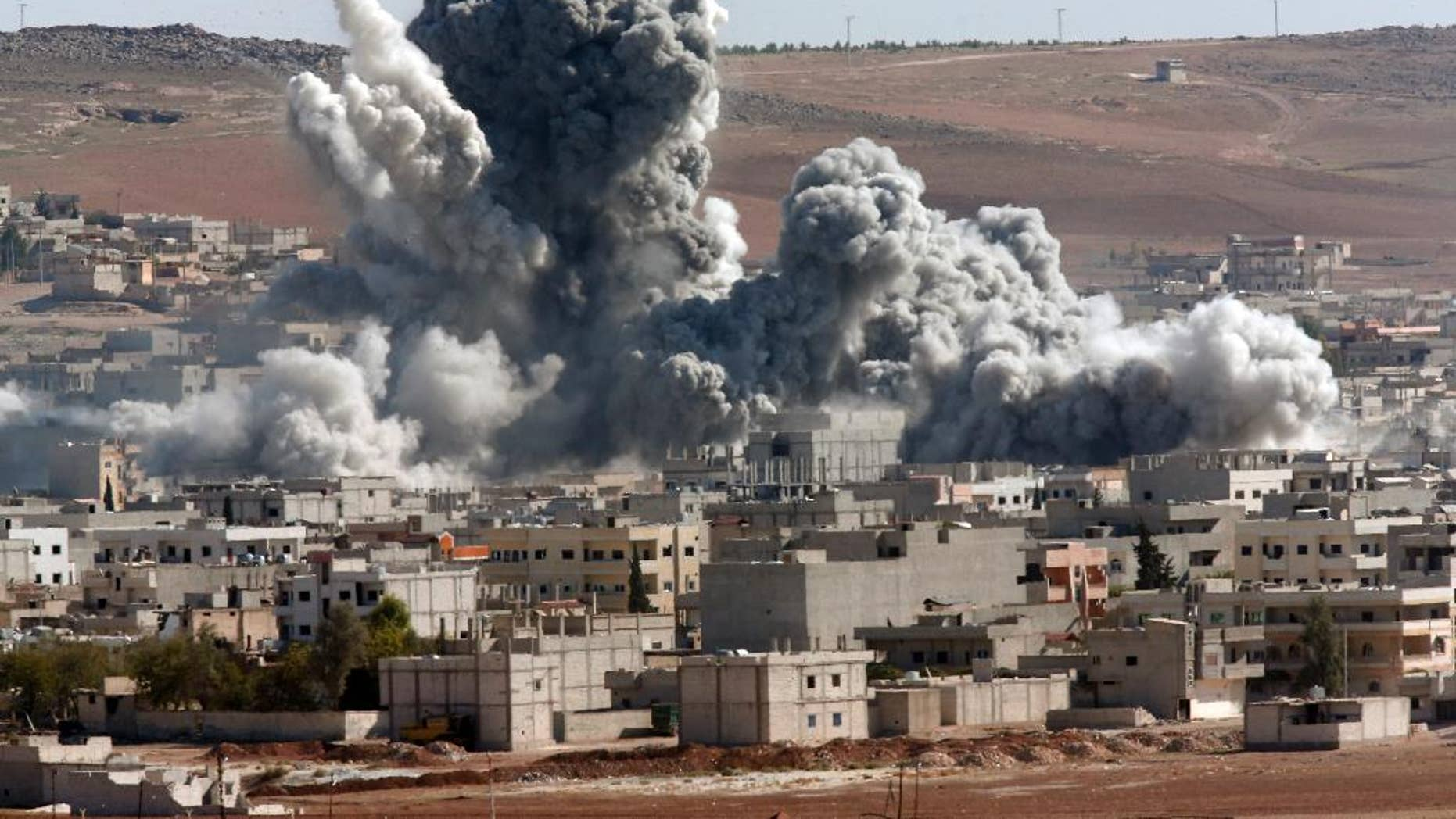 Oct. 22, 2014: Thick smoke from an airstrike by the US-led coalition rises in Kobani, Syria, as seen from a hilltop on the outskirts of Suruc, at the Turkey-Syria border. Kobani, also known as Ayn Arab, and its surrounding areas, has been under assault by extremists of the Islamic State group since mid-September and is being defended by Kurdish fighters.