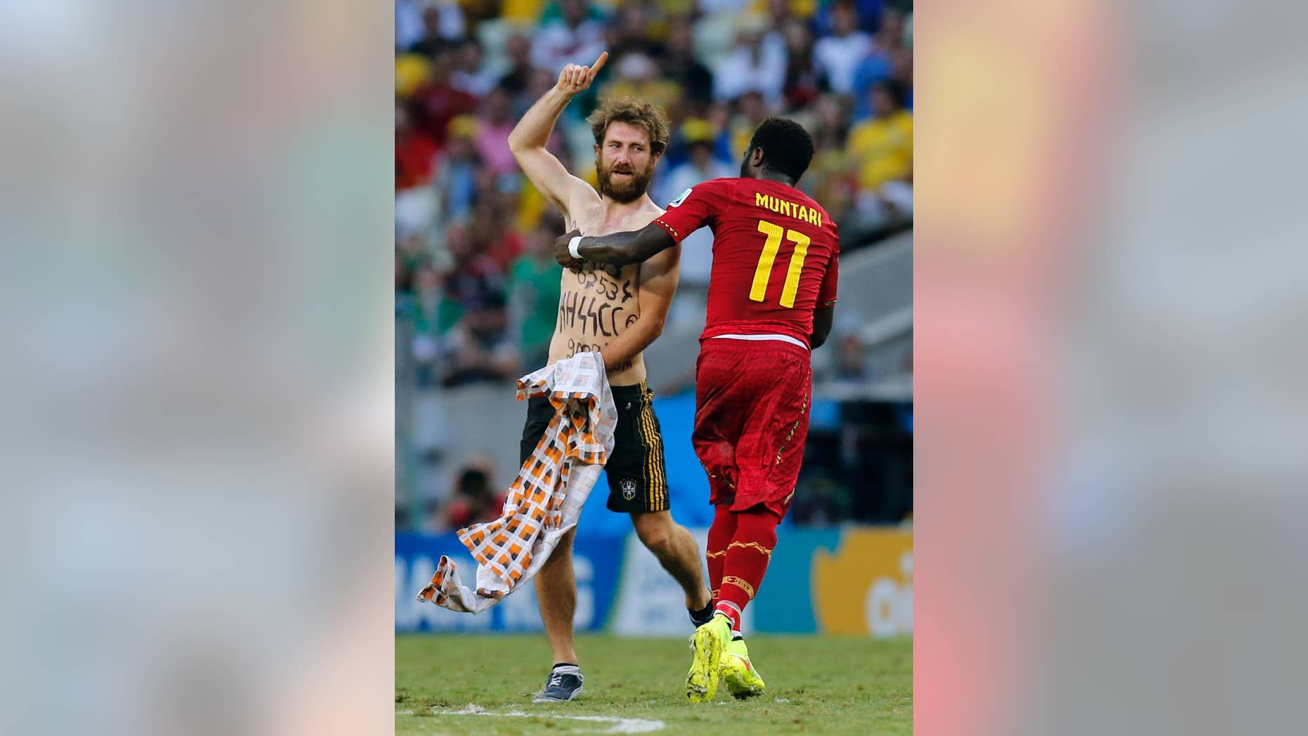 Ghana's Sulley Muntari assists a man off the pitch after he ran on during the group G World Cup soccer match between Germany and Ghana at the Arena Castelao in Fortaleza, Brazil, Saturday, June 21, 2014. (AP Photo/Frank Augstein)