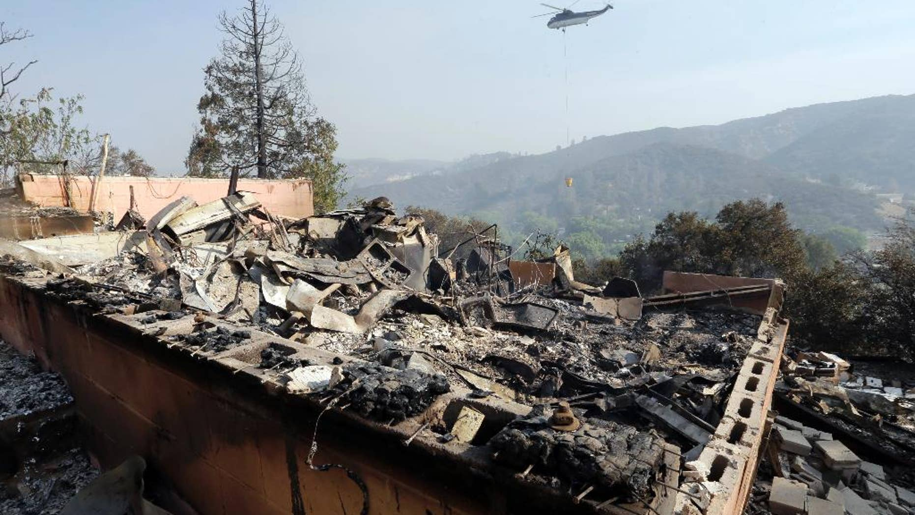 A firefighting helicopter carries a large water bucket behind a home that has been destroyed by a fire in Lake Hughes, Calif., in this June 2, 2013, photo.