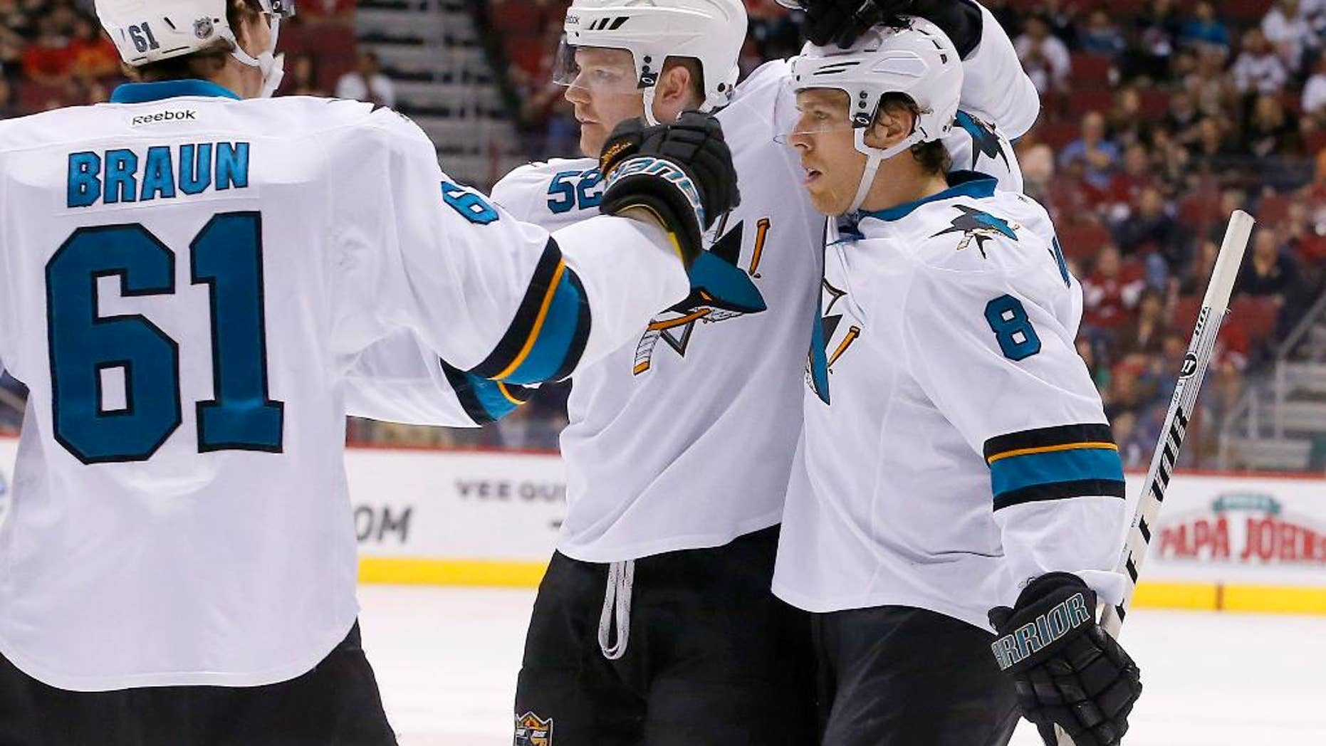 San Jose Sharks' Joe Pavelski (8) celebrates his second goal in the first period of an NHL hockey game against the Phoenix Coyotes with teammates Justin Braun (61) and Matt Irwin (52) on Saturday, April 12, 2014, in Glendale, Ariz. (AP Photo/Ross D. Franklin)