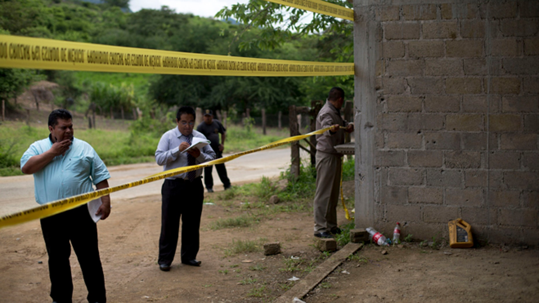 FILE - In this July 3, 2014 file photo, state authorities use crime scene tape to seal off an unfinished warehouse that was the site of a shootout between Mexican soldiers and alleged criminals on the outskirts of the village of San Pedro Limon in Mexico state, Mexico. Three soldiers have been charged with homicide in the June killings of 22 suspected gang members in southern Mexico, Attorney General Jesus Murillo Karam announced on Tuesday Sept. 30 2014. (AP Photo/Rebecca Blackwell, File)
