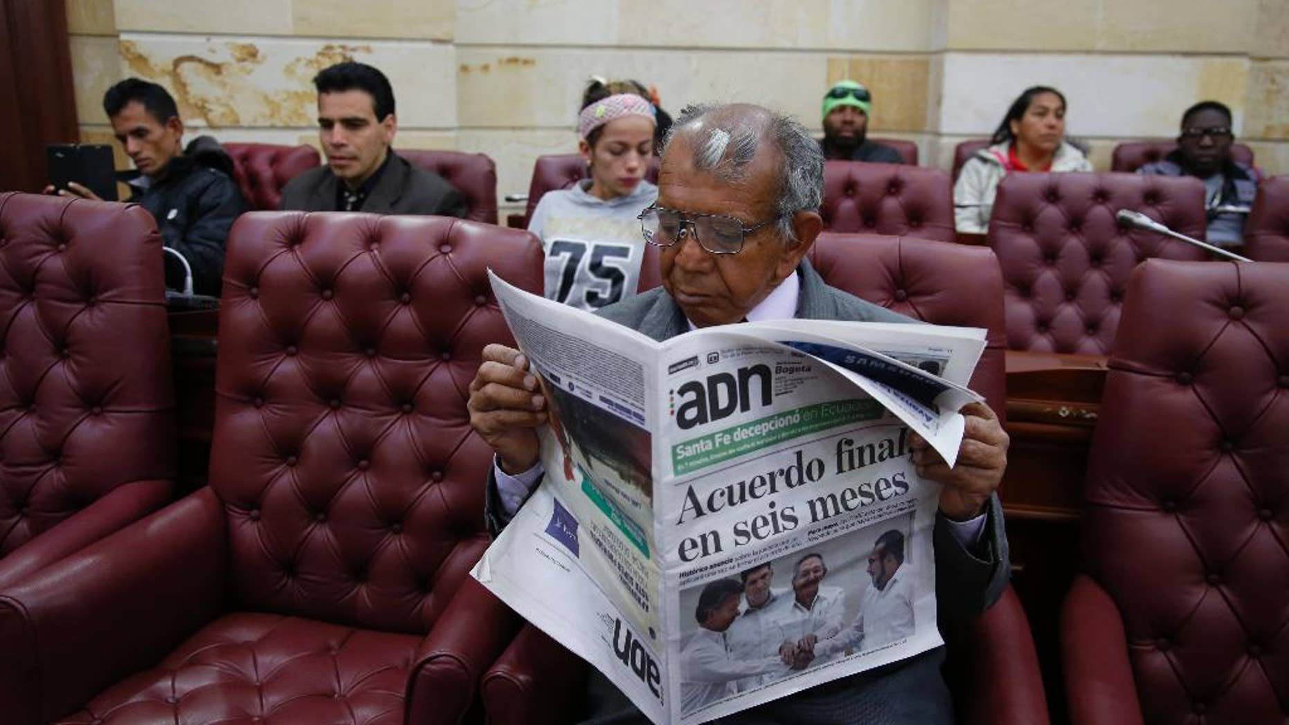 """Pedro Osuna Ramirez, 67, who says that he and his family were pushed from their land in central Colombia by rebels of the Revolutionary Armed Forces of Colombia, FARC, reads a newspaper during a hearing with victims of the guerrilla group inside Congress in Bogota, Colombia, Thursday, Sept. 24, 2015. Colombia's President Juan Manuel Santos and leaders of the FARC met in Havana on Wednesday, and vowed to end Latin America's longest-running armed conflict in the coming months. The newspaper's headline reads in Spanish """"Final agreement in six months."""" (AP Photo/Fernando Vergara)"""