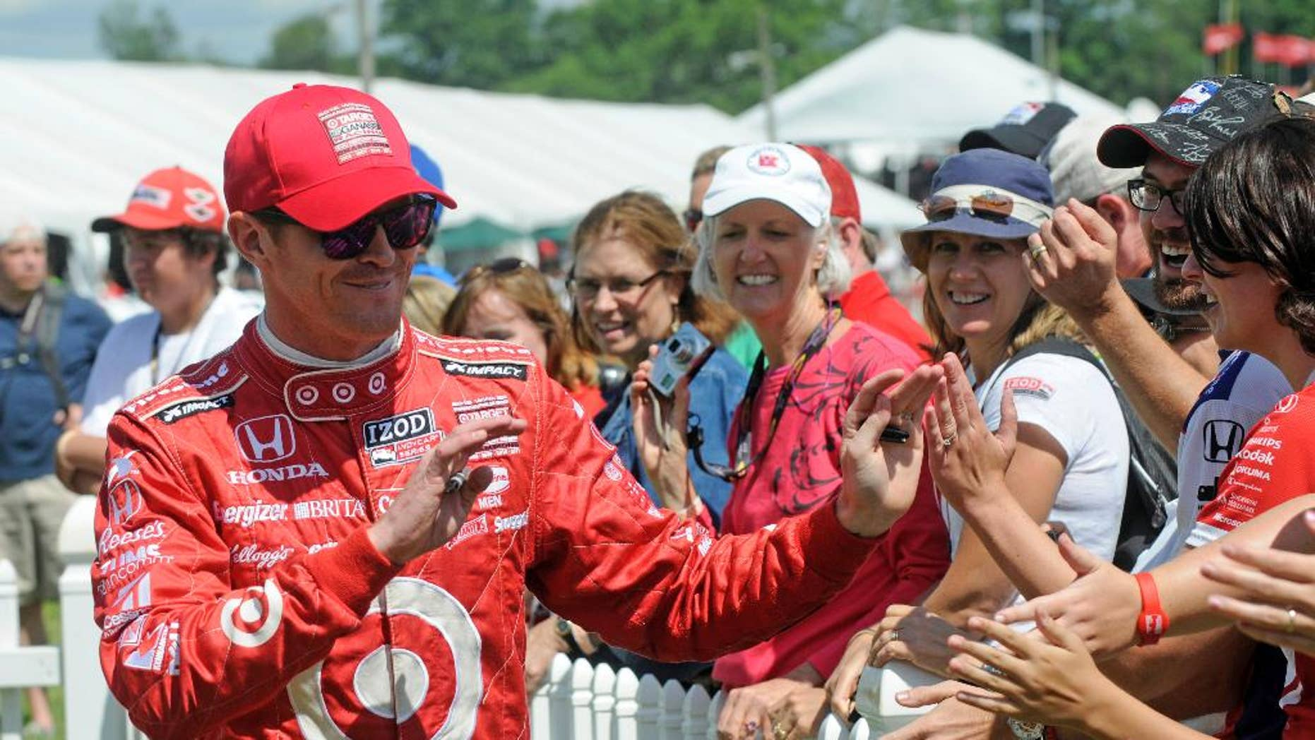 FILE - In this Aug. 4, 2013 file photo, Scott Dixon, of New Zealand, greets fans during driver introductions at the Honda Indy 200 at Mid-Ohio in Lexington, Ohio. Sponsors come and go in motor sports, where even the strongest partnerships can quickly unravel because of the economy, a difference of opinion or a change in marketing strategy. But Chip Ganassi has developed a partnership with Target that has lasted 25 years in counting, and the team owner considers the relationship with the retail giant a key element in the growth of his race team and Ganassi himself.  (AP Photo/Tom E. Puskar, File)