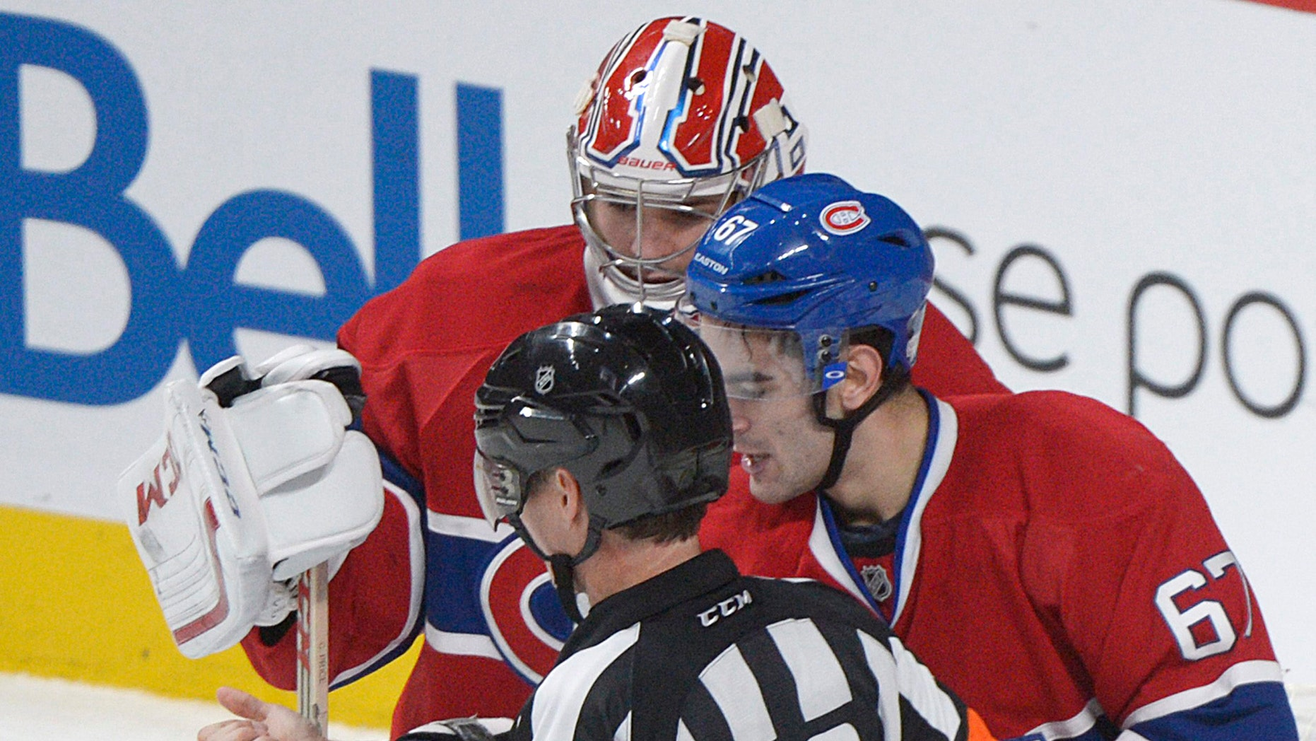 Montreal Canadiens' Max Pacioretty, right, shows his arm to a referee following an incident with Toronto Maple Leafs' Mikhail Grabovski as Canadiens' goaltender Carey Price looks on during third period NHL hockey action in Montreal, Saturday, Feb. 9, 2013. Grabovski has been accused of biting Pacioretty's arm. (AP Photo/The Canadian Press, Graham Hughes)