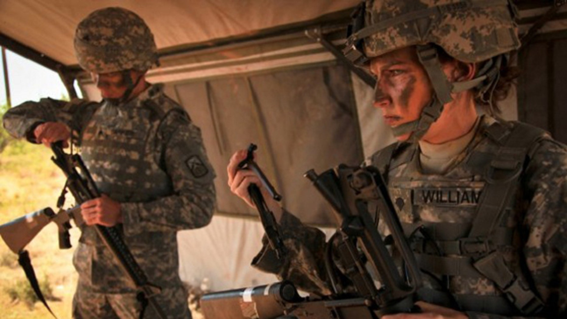 FILE: A female Army soldier tries on body armor.