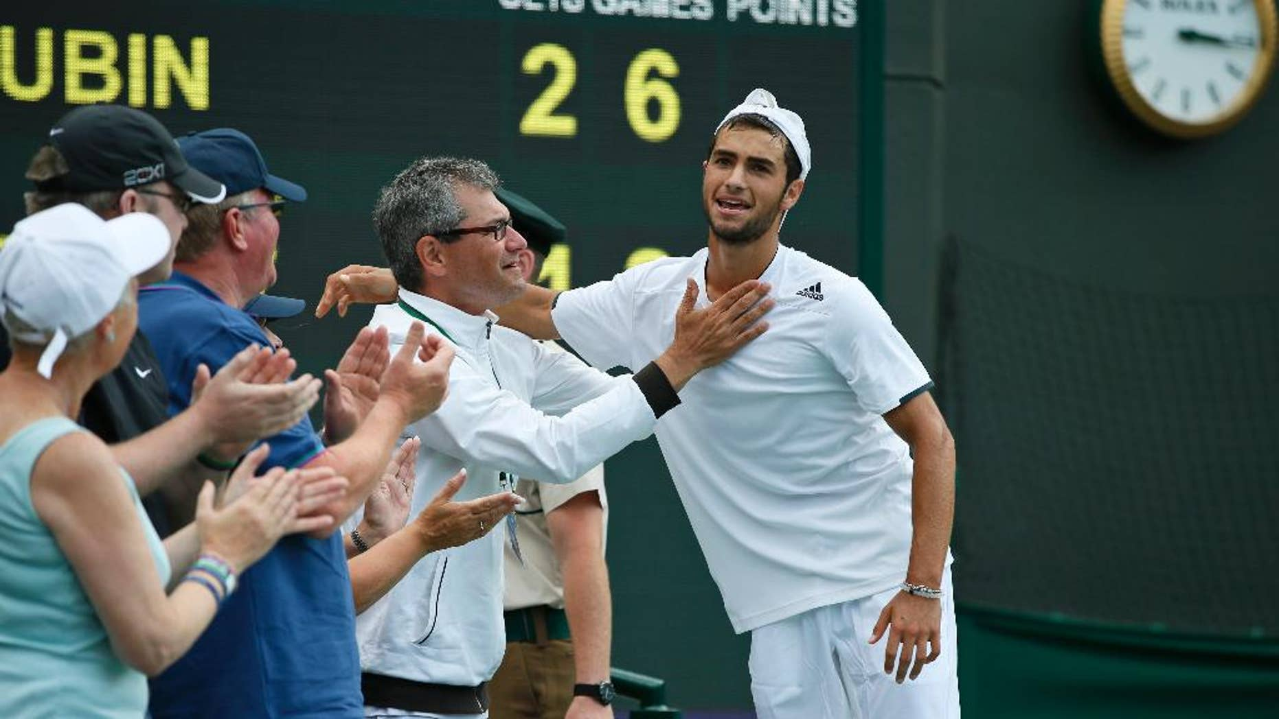 Noah Rubin of the U.S., right, is congratulated after defeating Stefan Kozlov of the U.S in the boys' singles final at the All England Lawn Tennis Championships in Wimbledon, London, Sunday July 6, 2014. (AP Photo/Alastair Grant)