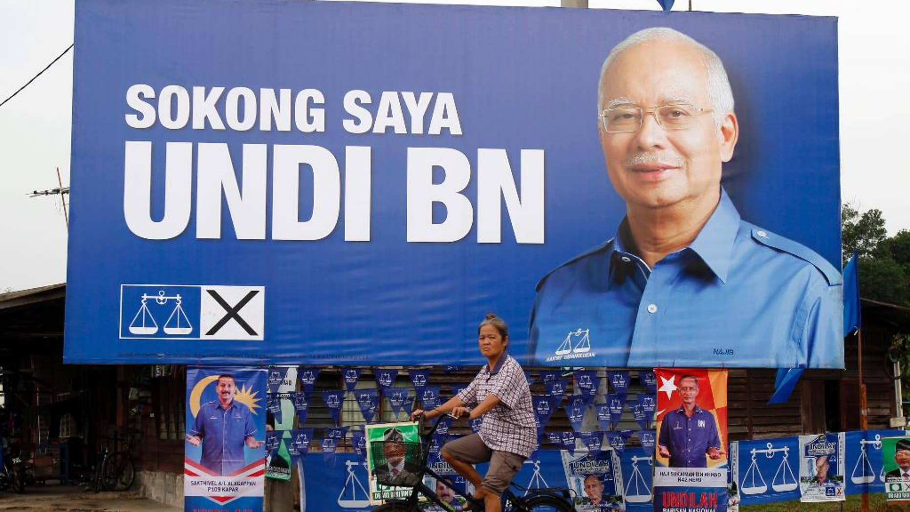 "FILE - In this May 3, 2013 file photo, a Malaysian ethnic Chinese woman rides past a billboard of Malaysia's ruling National Front coalition with a portrait of Prime Minister Najib Razak which translates ""I vote for National Front coalition"" ahead of the upcoming general elections in Klang, outside Kuala Lumpur, Malaysia. The party of Malaysia's scandal-tainted Prime Minister Najib Razak has won two parliamentary by-elections in a landslide, further strengthening his rule despite corruption allegations. (AP Photo/Lai Seng Sin, File)"