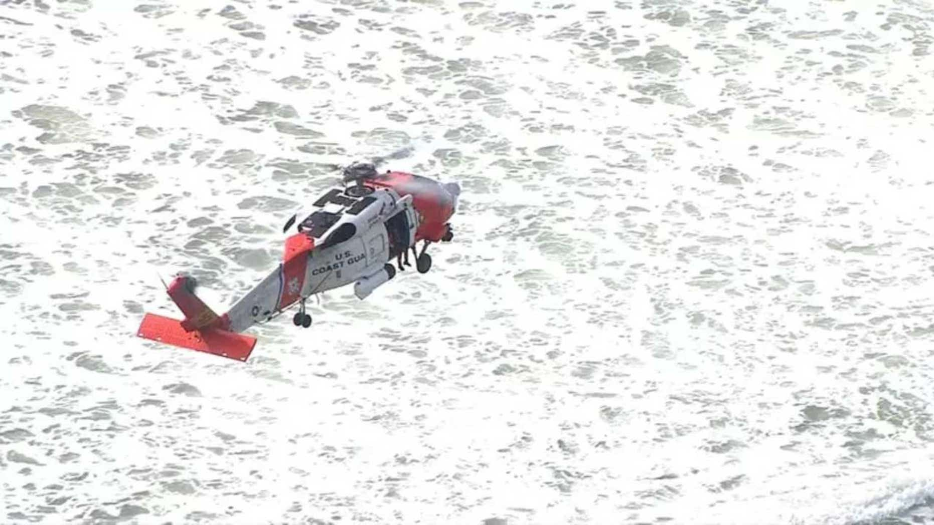 A U.S. Coast Guard helicopter crew searches Wednesday for a Fort Collins, Colo., teenager who reportedly fell into the surf off his boogie board off Rockaway Beach, Ore.