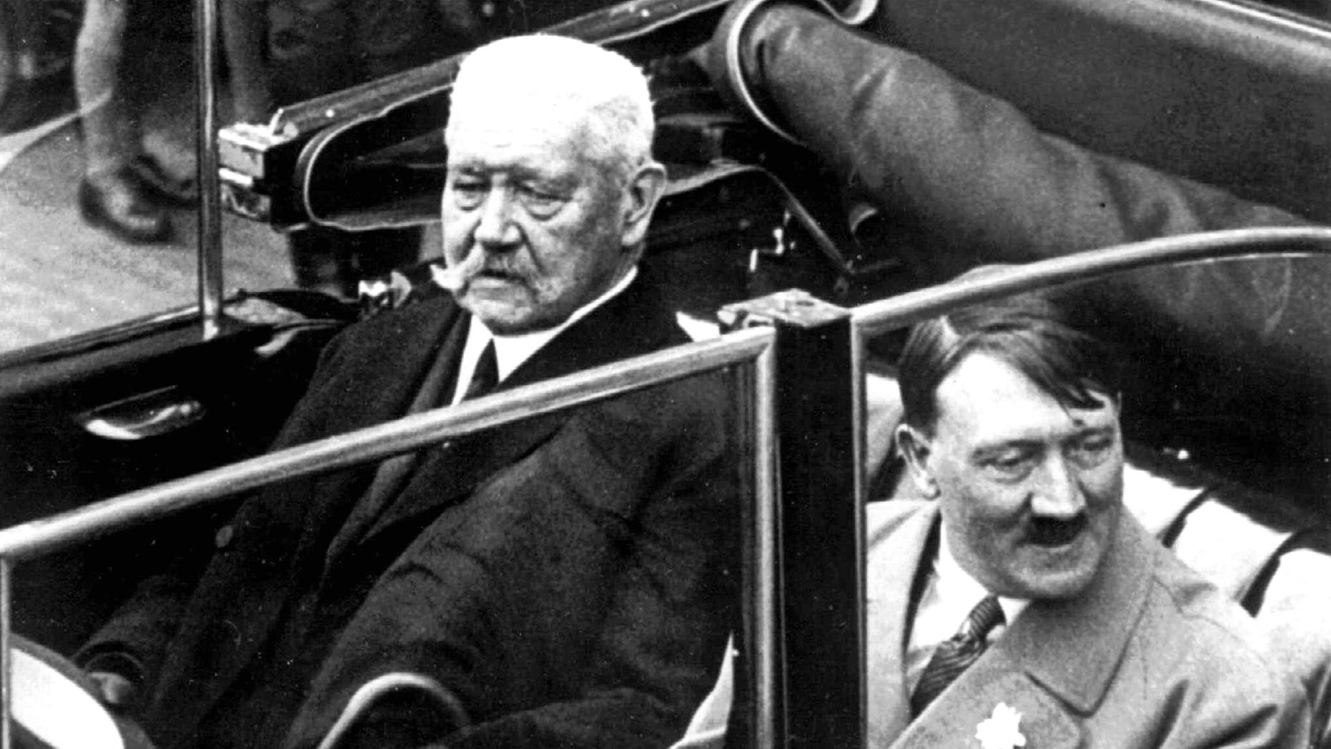 FILE  May 1, 1933 file photo shows German President Paul von Hindenburg, left, and Adolf Hitler, right, in a car  during a labor day celebration in Berlin. A Bavarian town has voted to strip Adolf Hitler of honorary citizenship bestowed upon him 80-years ago after an outcry prompted by their decision last week not to adopt a resolution denouncing the 1933 decision. The issue came up after an archivist discovered documents showing both Hitler and the president who appointed him, Paul von Hindenburg, had been given honorary citizenship of Dietramszell. A partial town council deadlocked in an 8-8 vote last week on the resolution, with councilors voting against saying it was not up to them to rewrite history. But town administrator Thomas Gerg said Wednesday Dec. 18, 2013 the full council voted Tuesday 21-0 both to adopt the resolution and nullify the citizenship for both men after hearing impassioned testimony from a woman who lost family in the Holocaust.  (AP Photo)