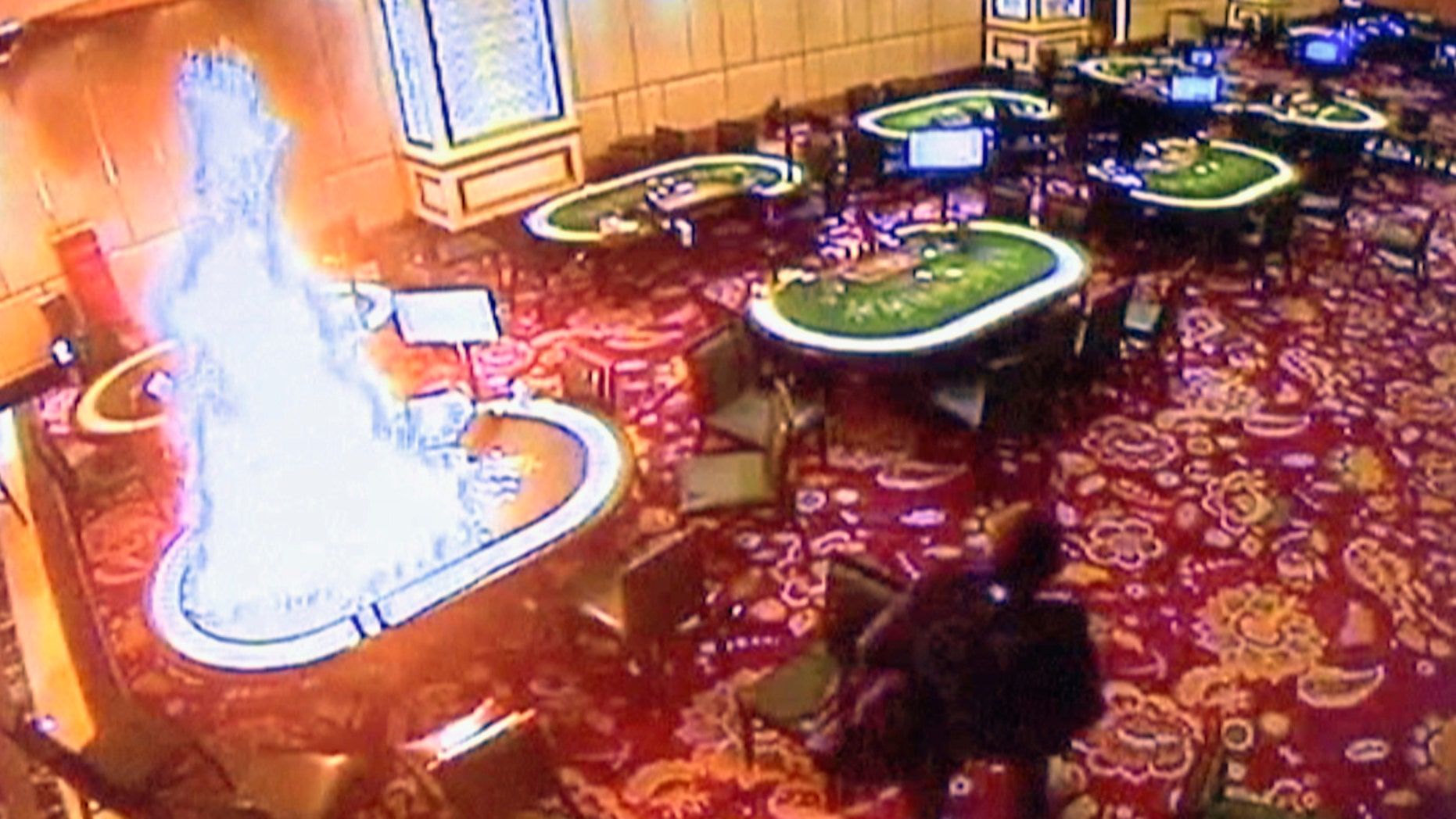 In this image made from security video released by Manila Police and Resorts World Manila on Saturday, June 3, 2017, a gunman walks away after setting fire to a gambling table in the Resorts World Manila entertainment and gambling complex in suburban Pasay city, southeast of Manila, Philippines on Friday, June 2, 2017.